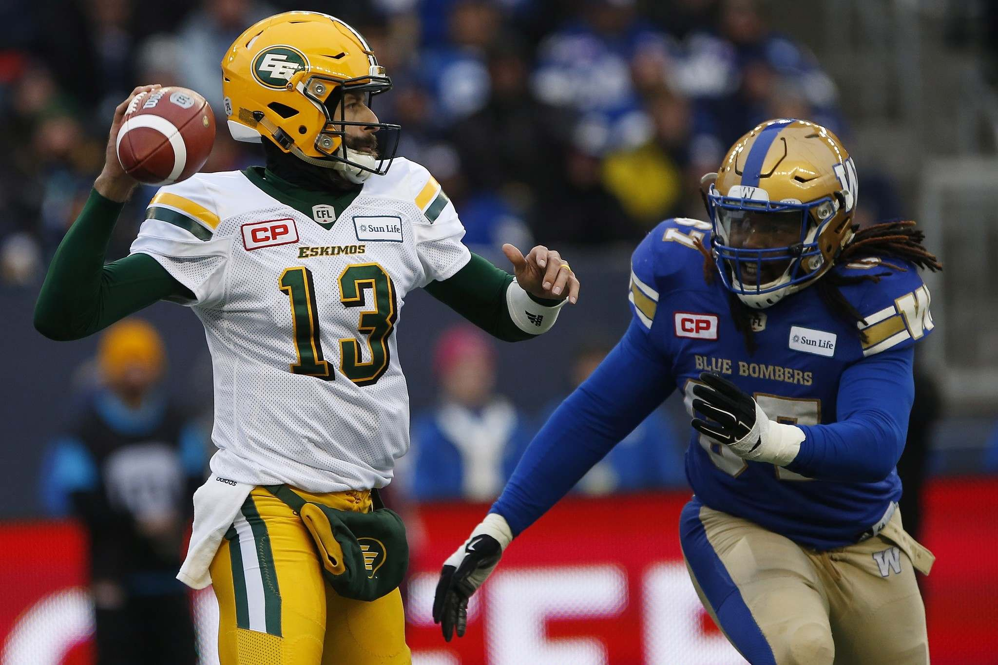 JOHN WOODS / THE CANADIAN PRESS</p><p>Edmonton Eskimos quarterback Mike Reilly (13) gets the pass away despite pressure from Winnipeg Blue Bombers&#39; Cory Johnson (67) during first half CFL western semifinal action in Winnipeg Sunday, November 12, 2017. </p>