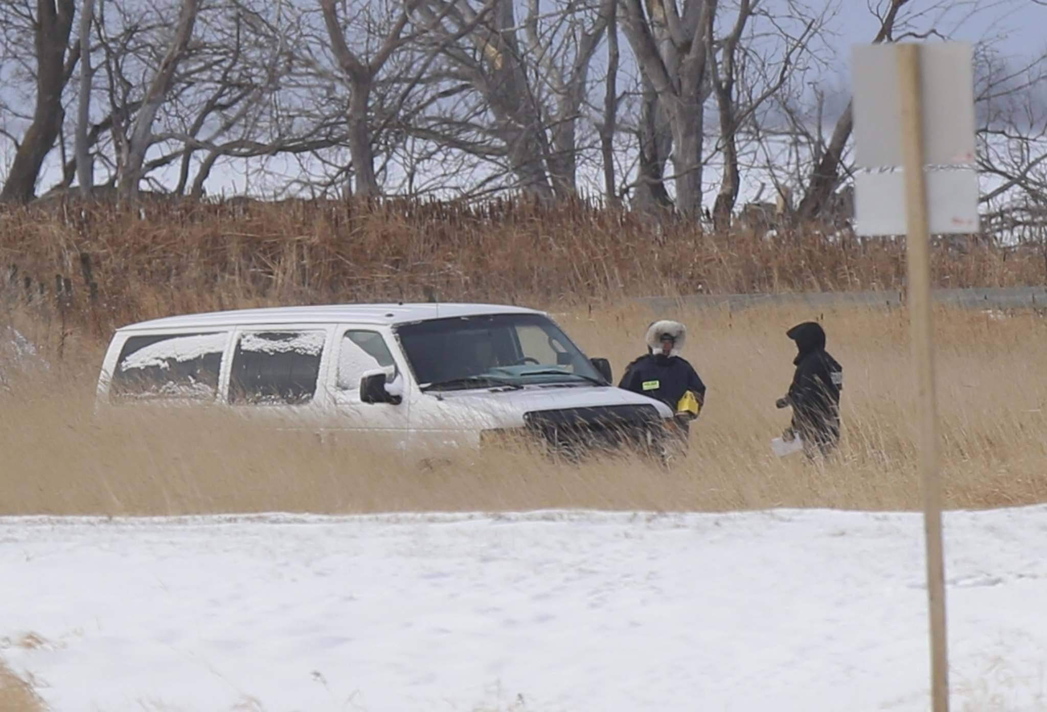 An unmarked white police van is seen at the bottom of a large snow-filled ditch off Highway 417 just south of the Lake Manitoba First Nation. (Wayne Glowacki / Winnipeg Free Press)</p>