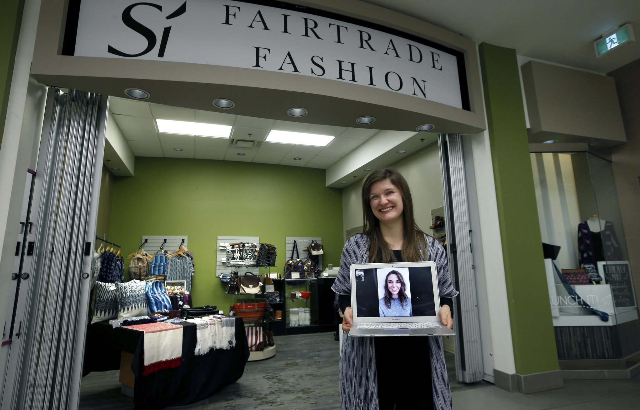 WAYNE GLOWACKI / WINNIPEG FREE PRESS</p><p>Ceilidh Moulden, co-owner of pop-up store Si Fairtrade Fashion in Cityplace, holds a laptop connected by Facetime to fellow co-owner Sarah Cullihall, who is from Winnipeg but is currently in Guatemala.</p>