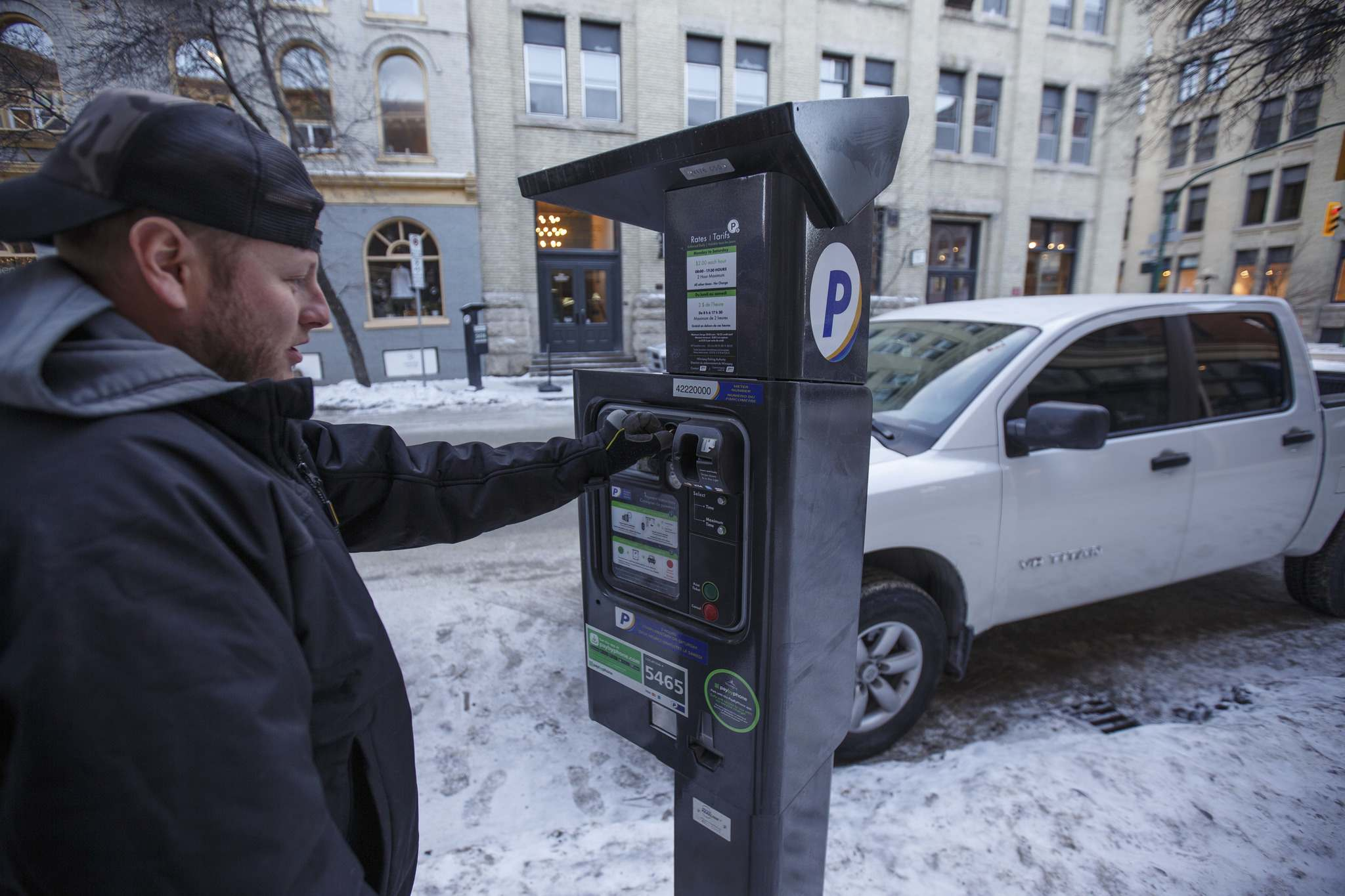 <p>Michael Matsyk plugs a meter with change Tuesday afternoon in the Exchange District. Some parking meters in the Exchange area have new stickers on them explaining the hourly rates. The stickers offering two free hours on Saturdays are still there as well.</p>