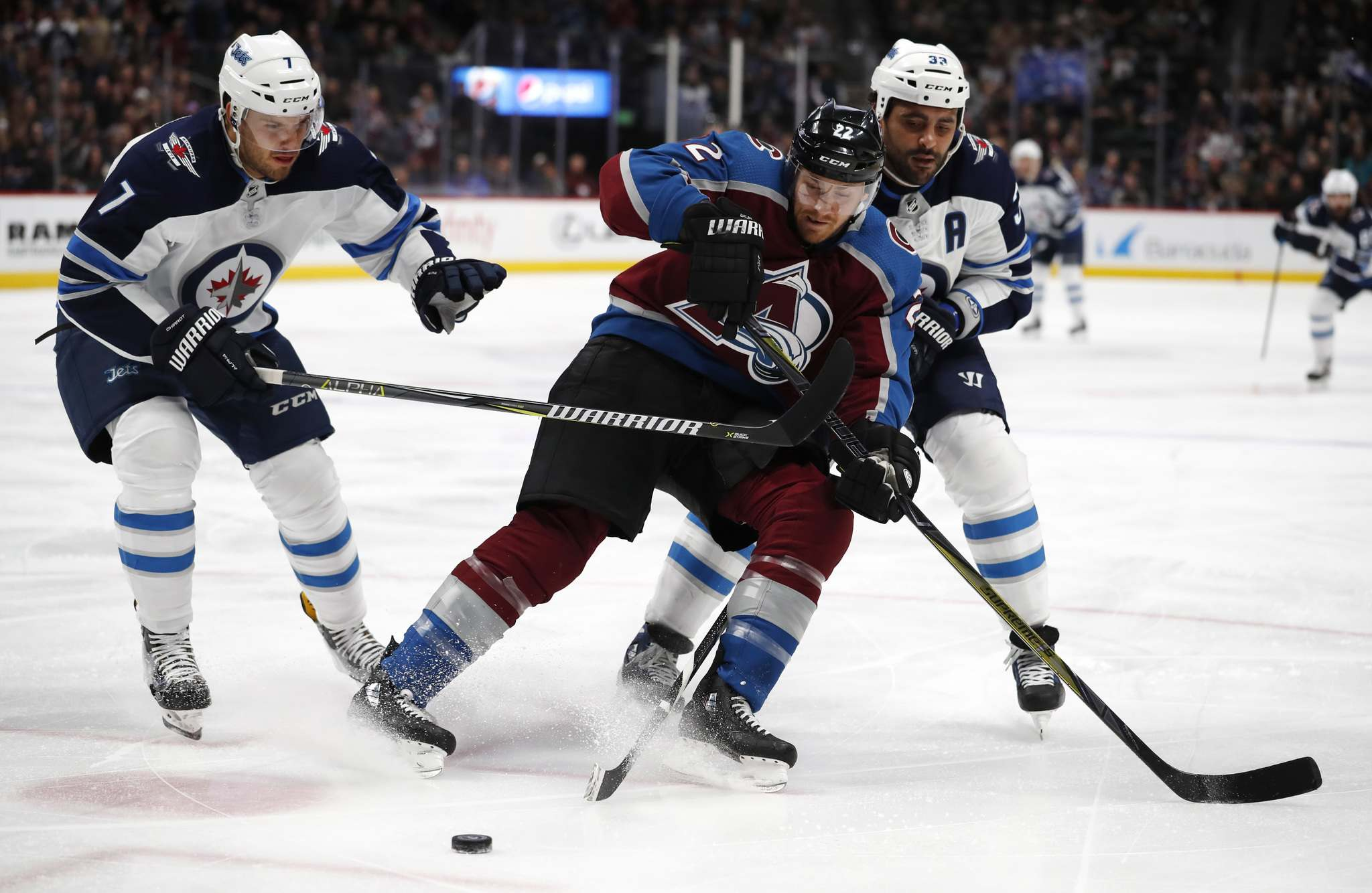 <p>Colorado Avalanche center Colin Wilson, center, is tied up by Winnipeg Jets defensemen Ben Chiarot, left, and Dustin Byfuglien while pursuing the puck in the first period of an NHL hockey game Tuesday, Jan. 2, 2018, in Denver. </p>