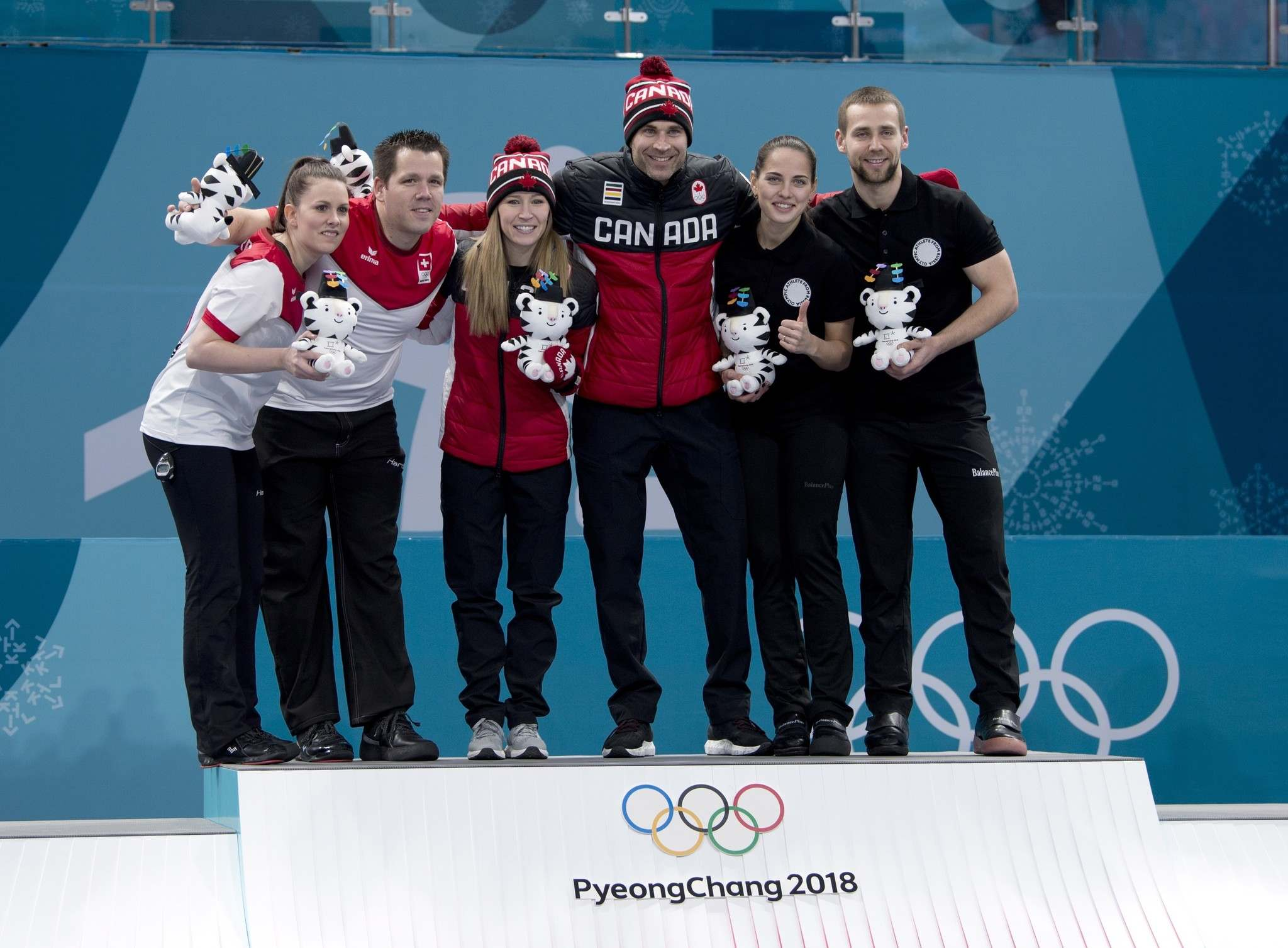 Mixed doubles gold medal winners Canadians Kaitlyn Lawes and John Morris, centre, silver medal winners , Jenny Perret and Martin Rios, of Switzerland, left, and bronze medal Anastasia Bryzgalova and Alexandr Krushelnitckii, of Russia, celebrate at the 2018 Olympic Winter Games in Gangneung, South Korea on Tuesday, February 13, 2018. (Michael Burns / The Canadian Press)</p>