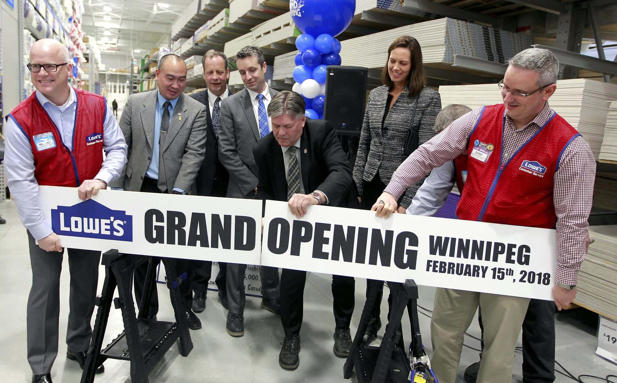 BORIS MINKEVICH / WINNIPEG FREE PRESS</p><p>Provincial Education Minister Ian Wishart (centre) performs the ceremonial board-cutting with VIPs and local politicians at the new Lowe's, located in the Linden Ridge Shopping Centre.</p>