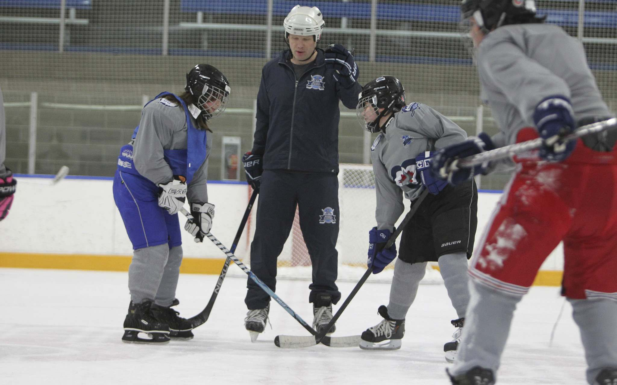 Cale David, an instructor from Price Industries, drops the puck during a scrimmage for Grade 6 and 7 students from Chief Peguis Junior High. (Ruth Bonneville / Winnipeg Free Press)
