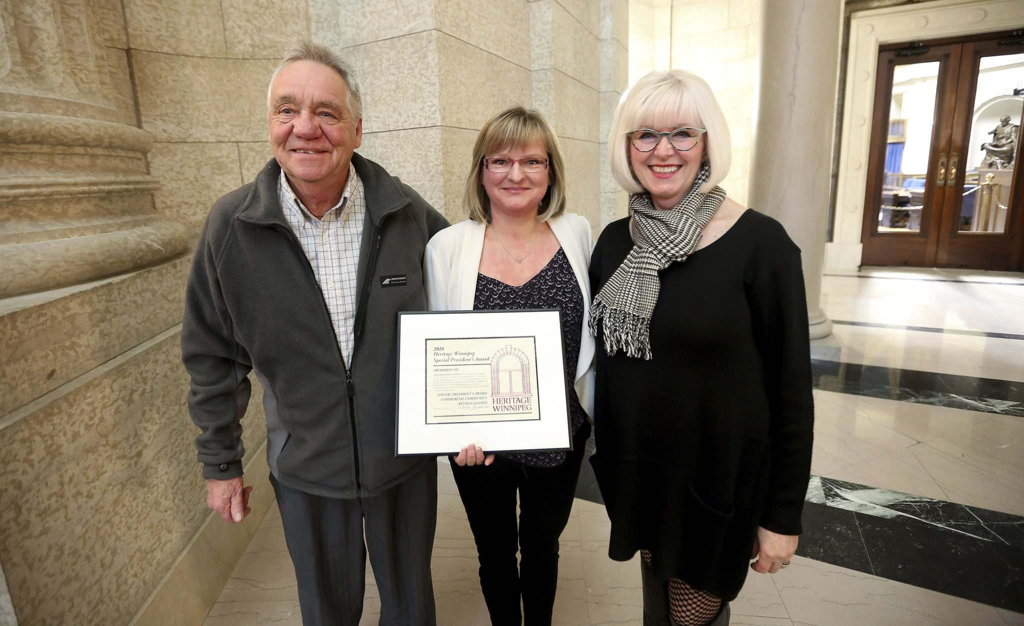 Shelley Armstrong, middle, with her father, George, left, was recognized for the family's work on the Langside Grocery by Lisa Gardewine, Heritage Winnipeg President. (Trevor Hagan / Winnipeg Free Press)</p>