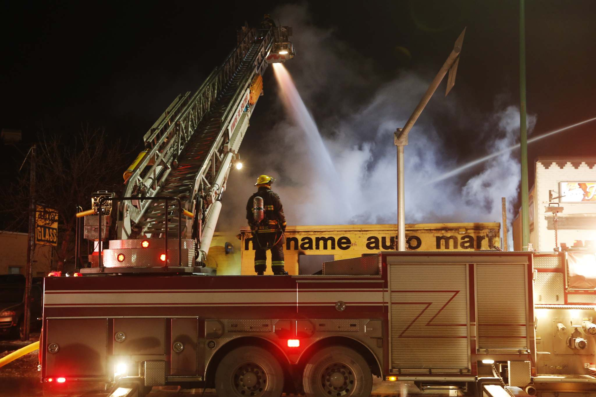 JOHN WOODS / WINNIPEG FREE PRESS</p><p>Firefighters work on a fire at a No Name Auto Mart at 951 Portage Ave. on Tuesday night.</p>