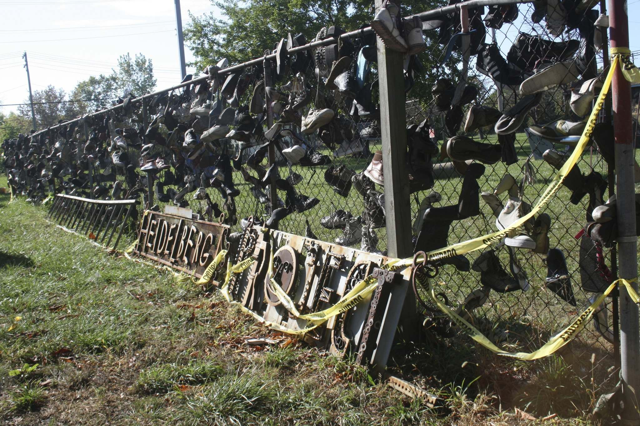 A fence on Heidelberg Street is covered in old, worn shoes.</p>