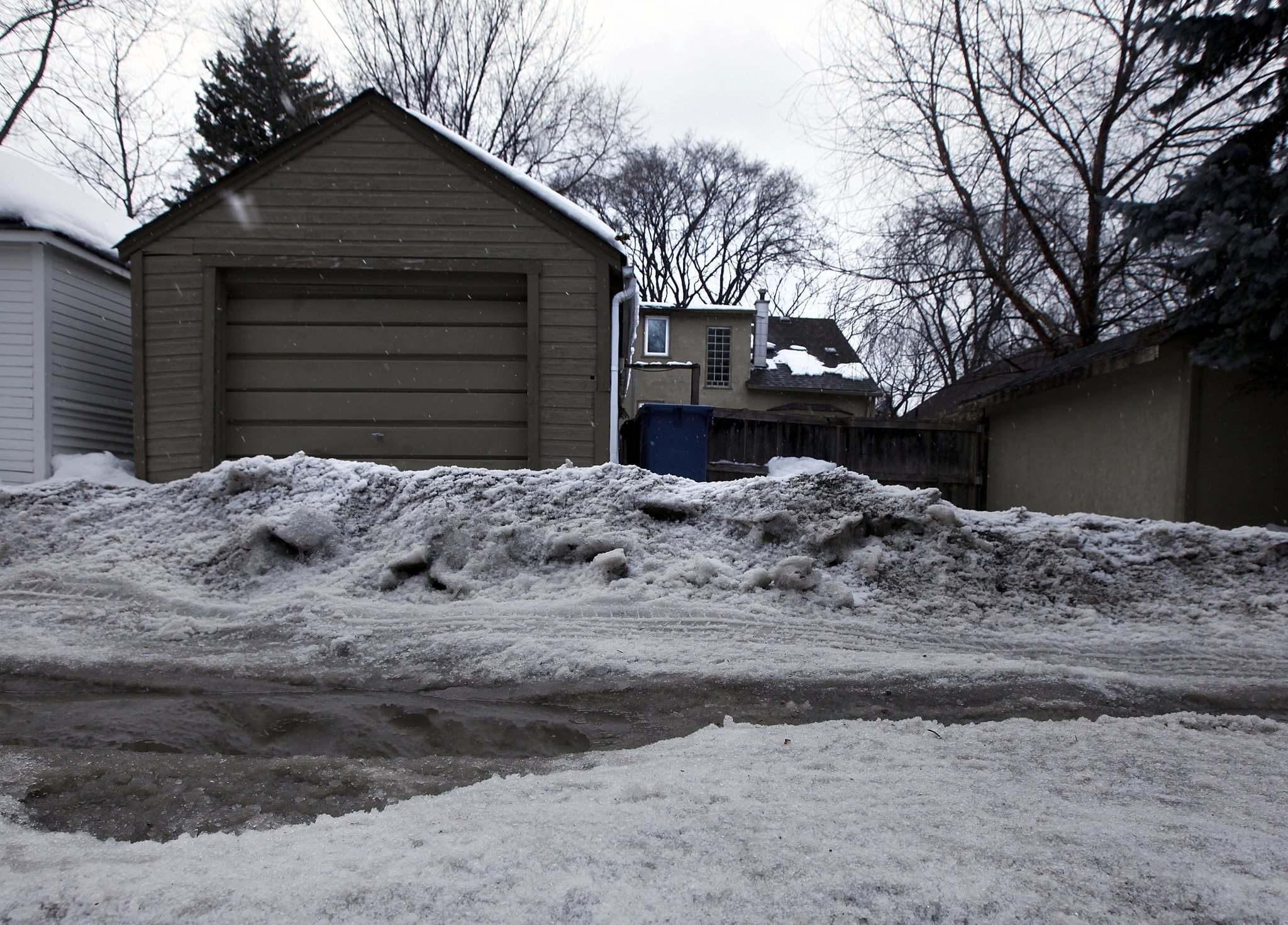 A tall windrow of ice sits in front of a back-lane garage behind the 400 block of Waterloo Street. (Phil Hossack / Free Press files)