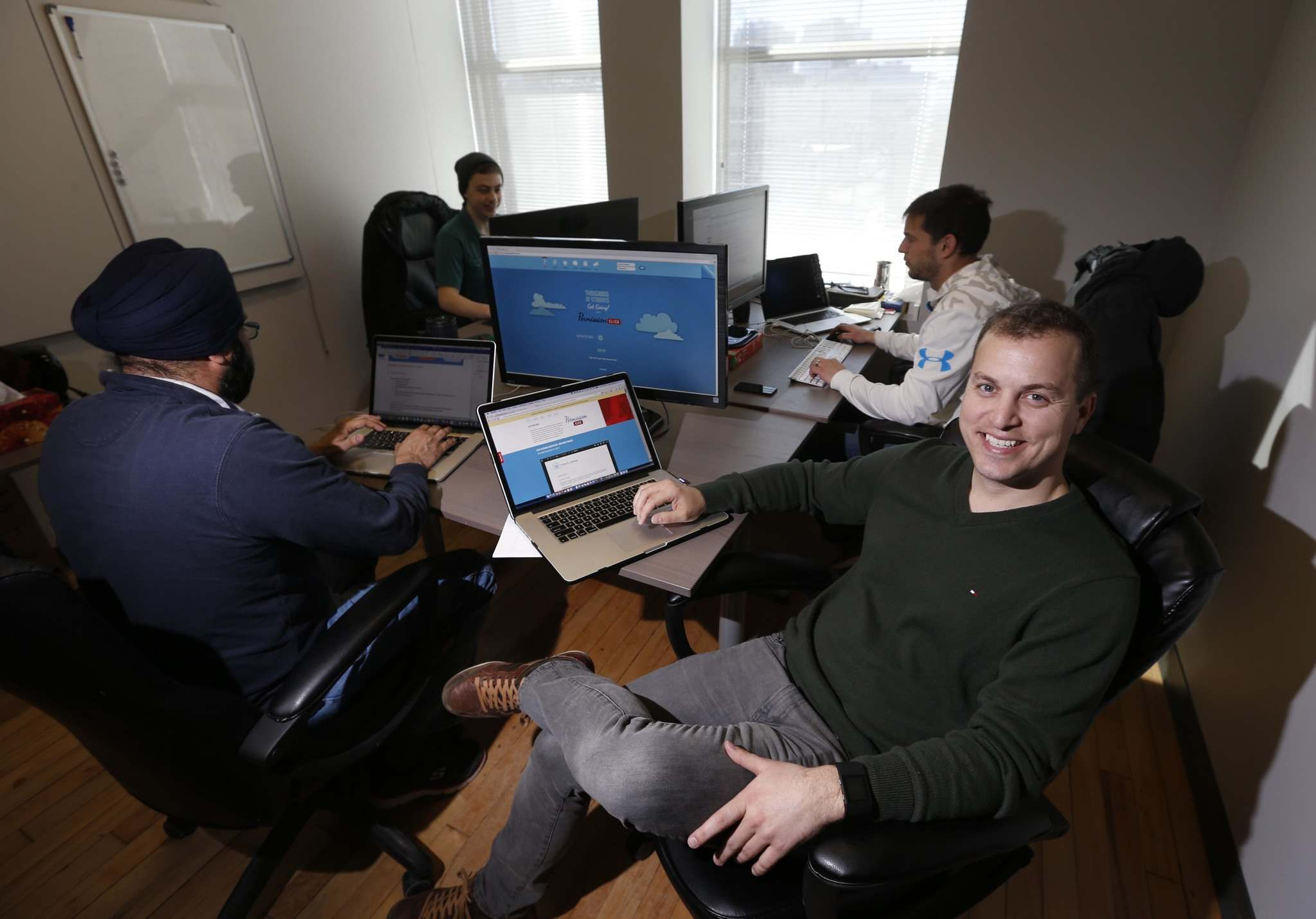 WAYNE GLOWACKI / WINNIPEG FREE PRESS FILES</p><p>Chris Johnson, centre, is CEO of Permission Click, a Winnipeg company that&rsquo;s developed digital permission forms and automatic payment system for schools and clubs across North America.</p>