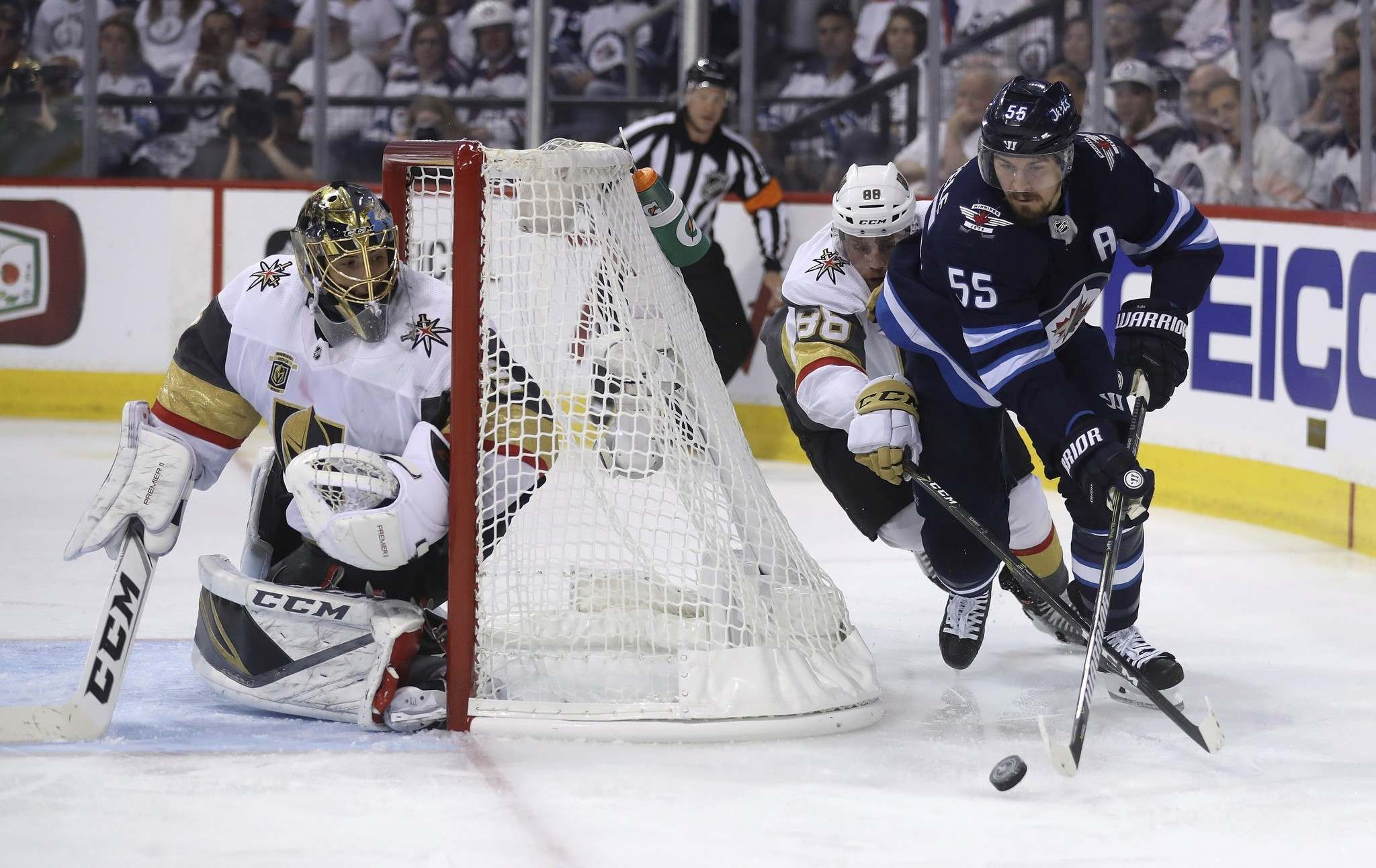 <p>Winnipeg Jets&#39; Mark Scheifele drives behind Vegas Golden Knights&#39; goaltender Marc-Andre Fleury with Nate Schmidt trailing behind during the second period.</p>
