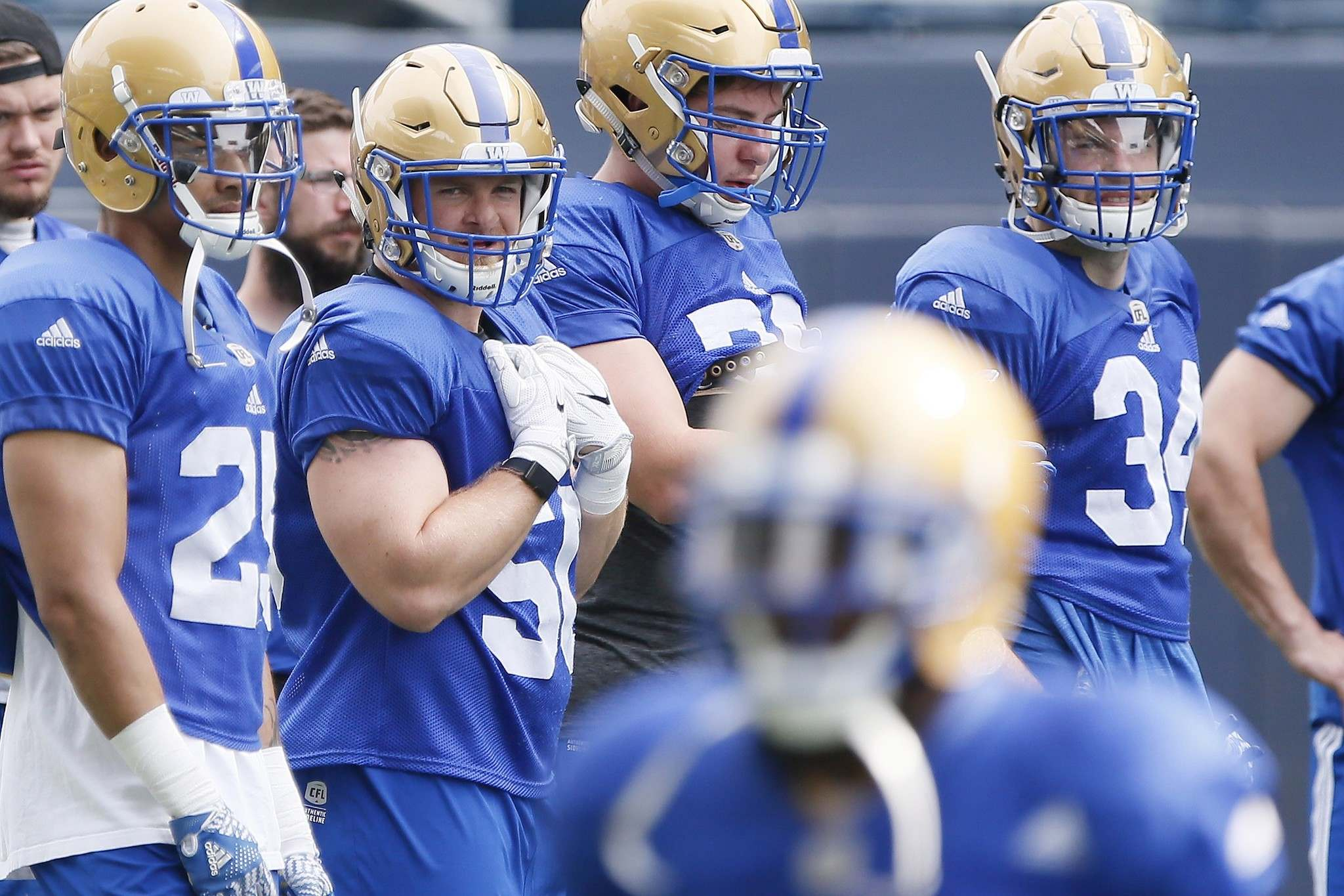 <p>New addition to the Winnipeg Blue Bombers Adam Bighill, second from left, watches drills at training camp in Winnipeg Thursday.</p>