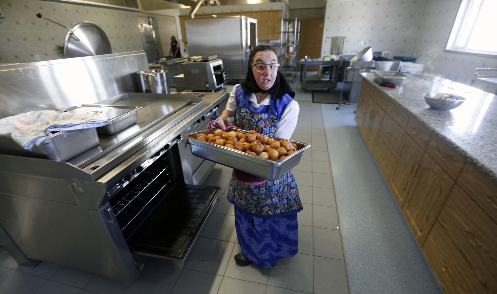 PHIL HOSSACK/Winnipeg Free Press</p><p>Melissa Hofer removes cooked dumplings from an oven the James Valley Hutterite Colony.</p>