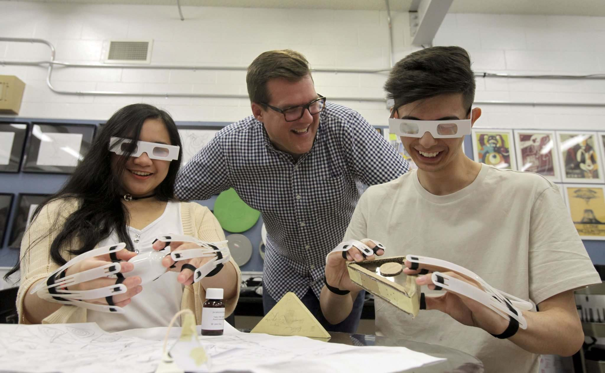 ERIK PINDERA / WINNIPEG FREE PRESS</p><p>Sisler High School teacher Jamie Leduc watches Denise Diosana (left) and Marcelo Aiello as they try to grab salt shakers with vision-impairing glasses and dexterity-reducing gloves.</p>