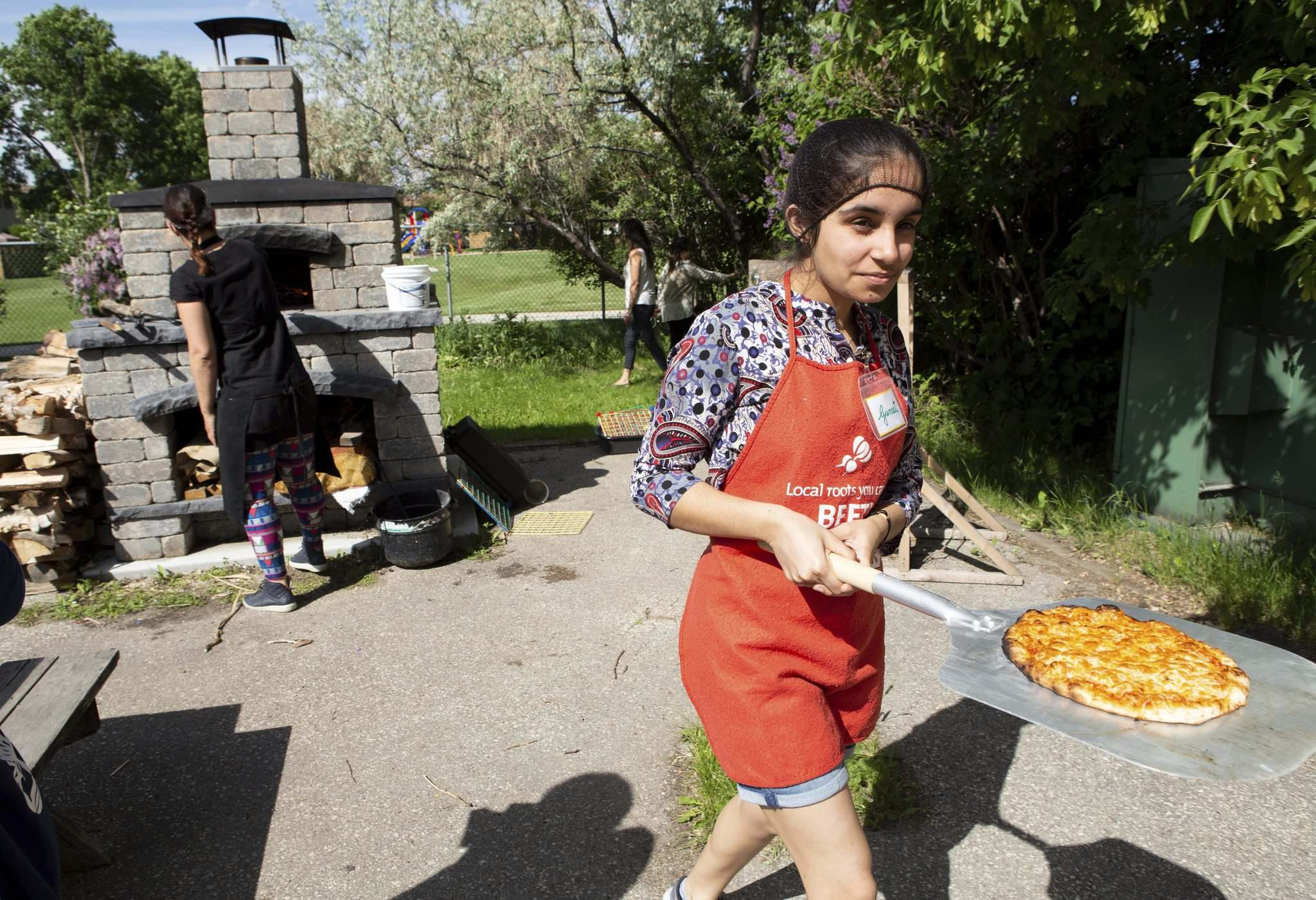 Guneet Uppal walks the first of the pizza from the oven.