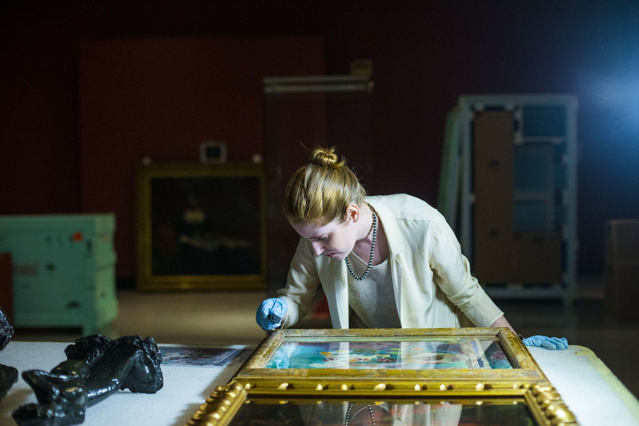 <p>Conservator Erin Anderson inspects paintings as they are uncrated at the gallery.</p>