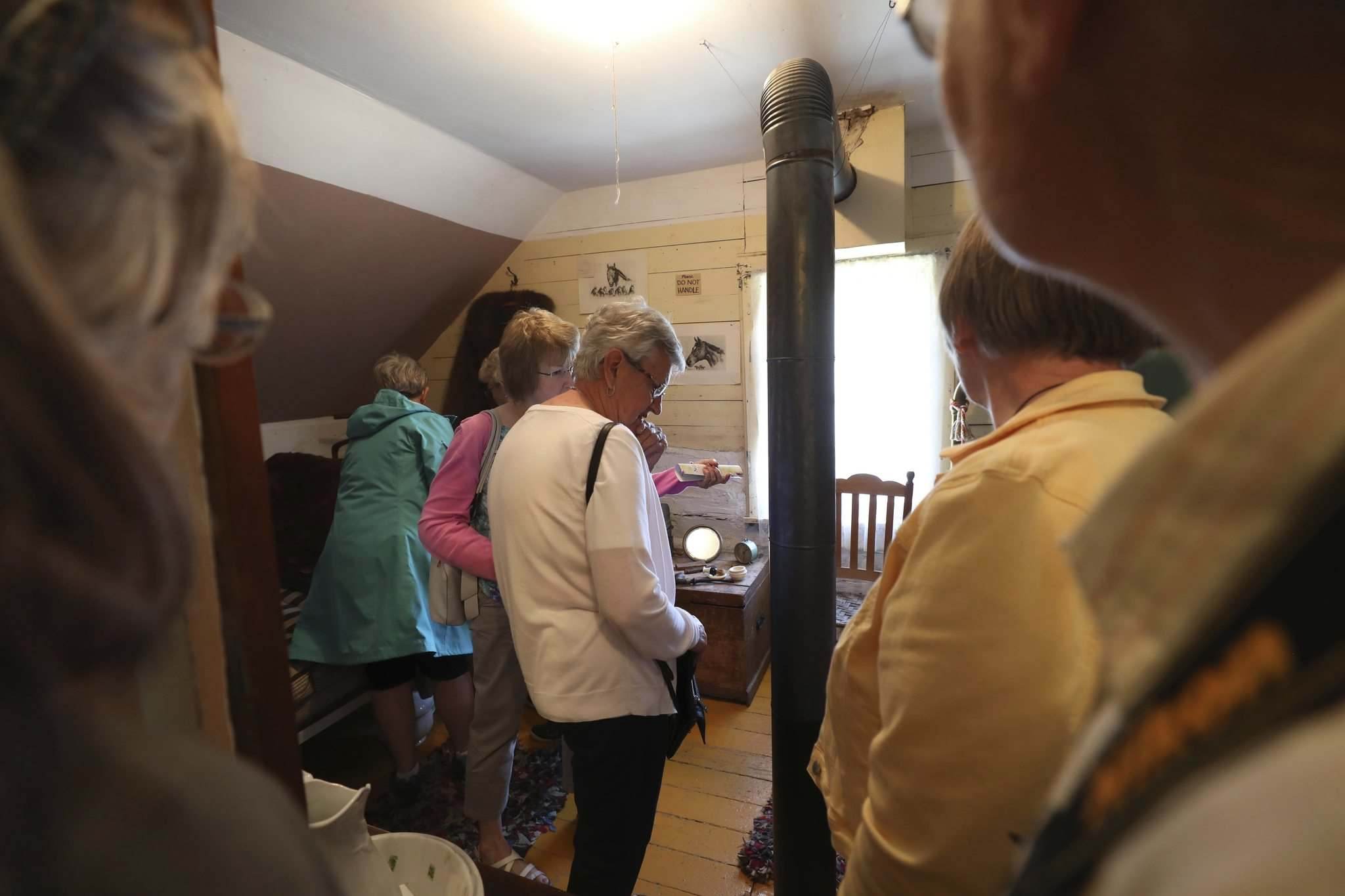 A group tours one of the upstairs bedrooms in Hazel Cottage.