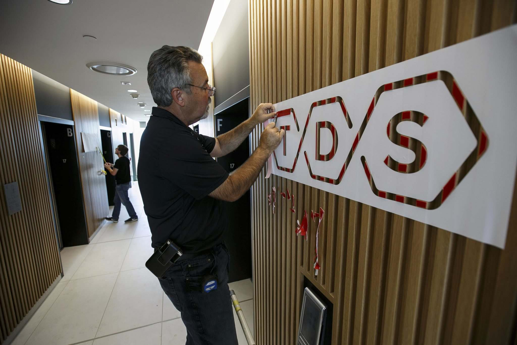 Larry Neudorf installs the TDS law firm logo in the elevator lobby on the 17th floor of their new offices. (Mike Deal / Winnipeg Free Press)</p>