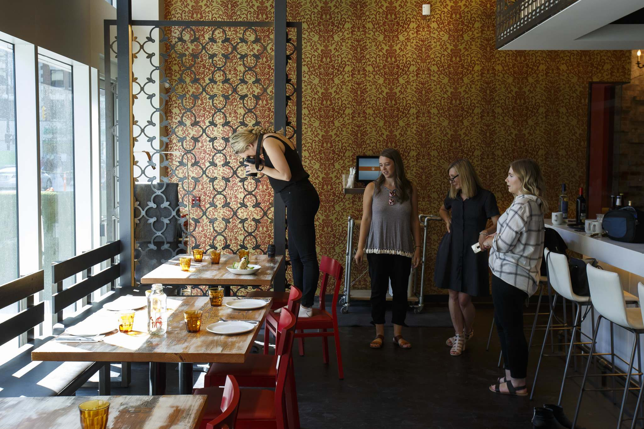 Photographer Lauren Siddall photographs a plate of food from The Merchant Kitchen's menu.