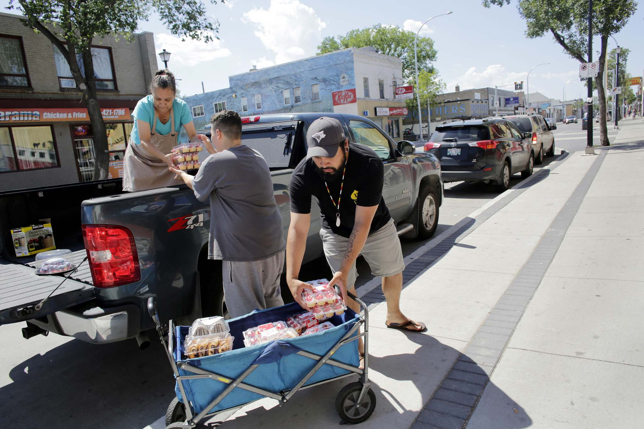 Loretta Stevenson (from left), Shaina Zabinski and Justin Kalinouski unload food at the Makoonsag Intergenerational Children's Centre.