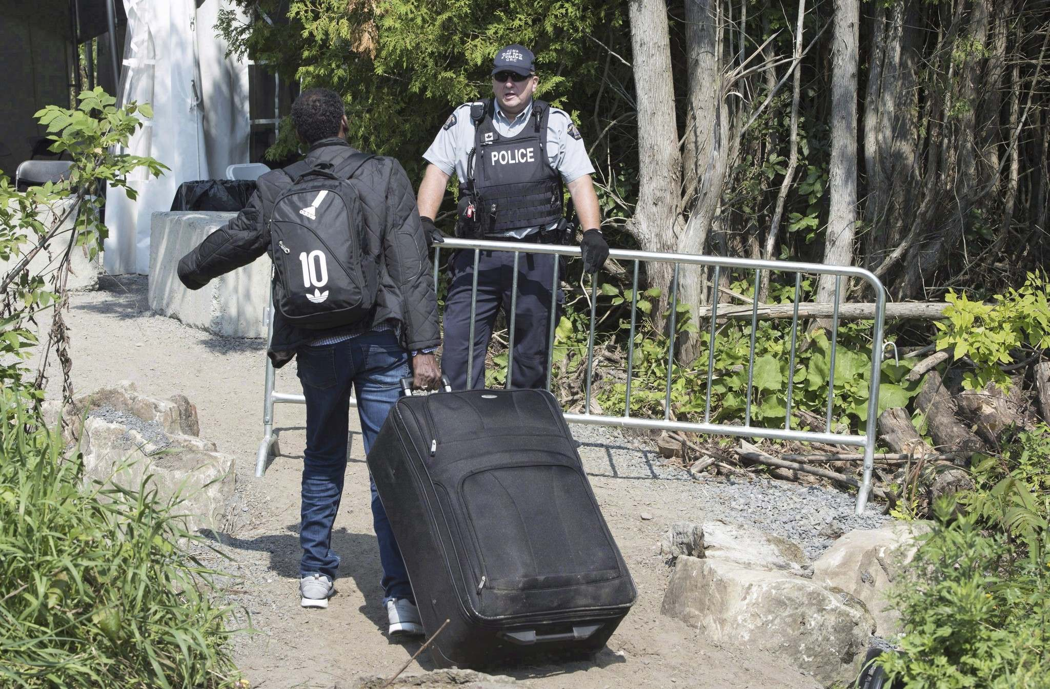 """THE CANADIAN PRESS/Paul Chiasson</p><p>An asylum seeker, claiming to be from Eritrea, is confronted by an RCMP officer as he crosses the border into Canada. A new poll has found 76 per cent of Manitoba respondents agreed with the statement: """"This situation is a crisis – Canada's ability to handle the situation is at a limit.""""</p>"""