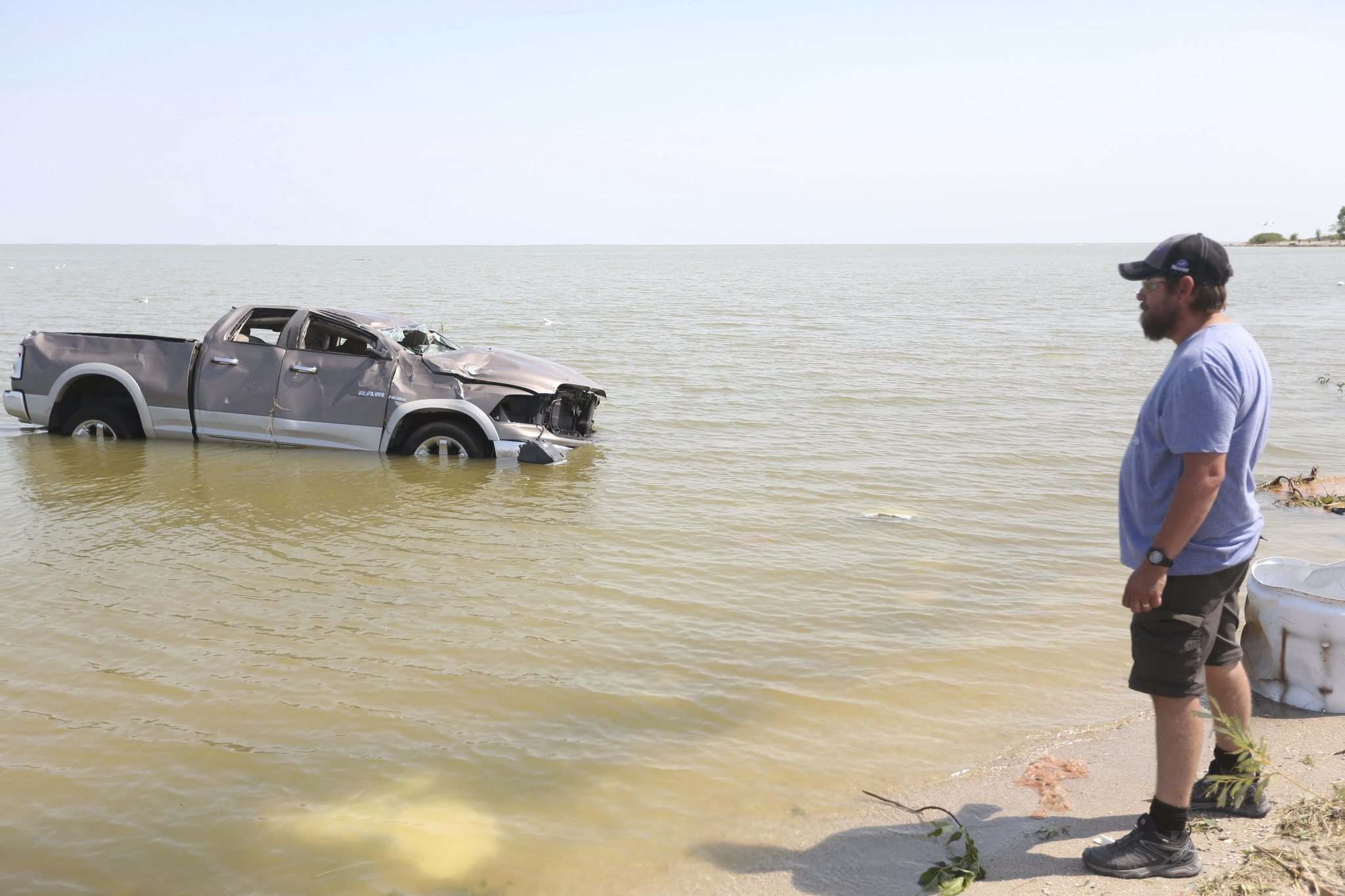 Shawn Gurke, a resident of Alonsa, watches a truck floating in Lake Manitoba after a tornado hit on Friday. (Melissa Verge / Brandon Sun)</p>