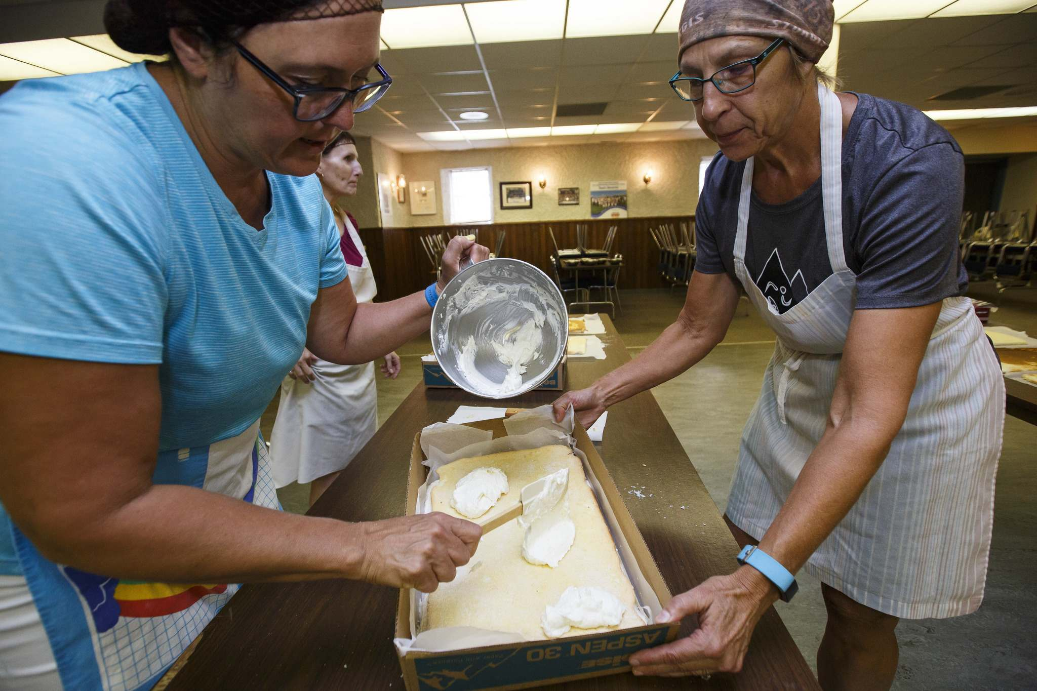 Hilda Terry (left) and Alenia Howell add a final layer of cream filling to the lemon torte.