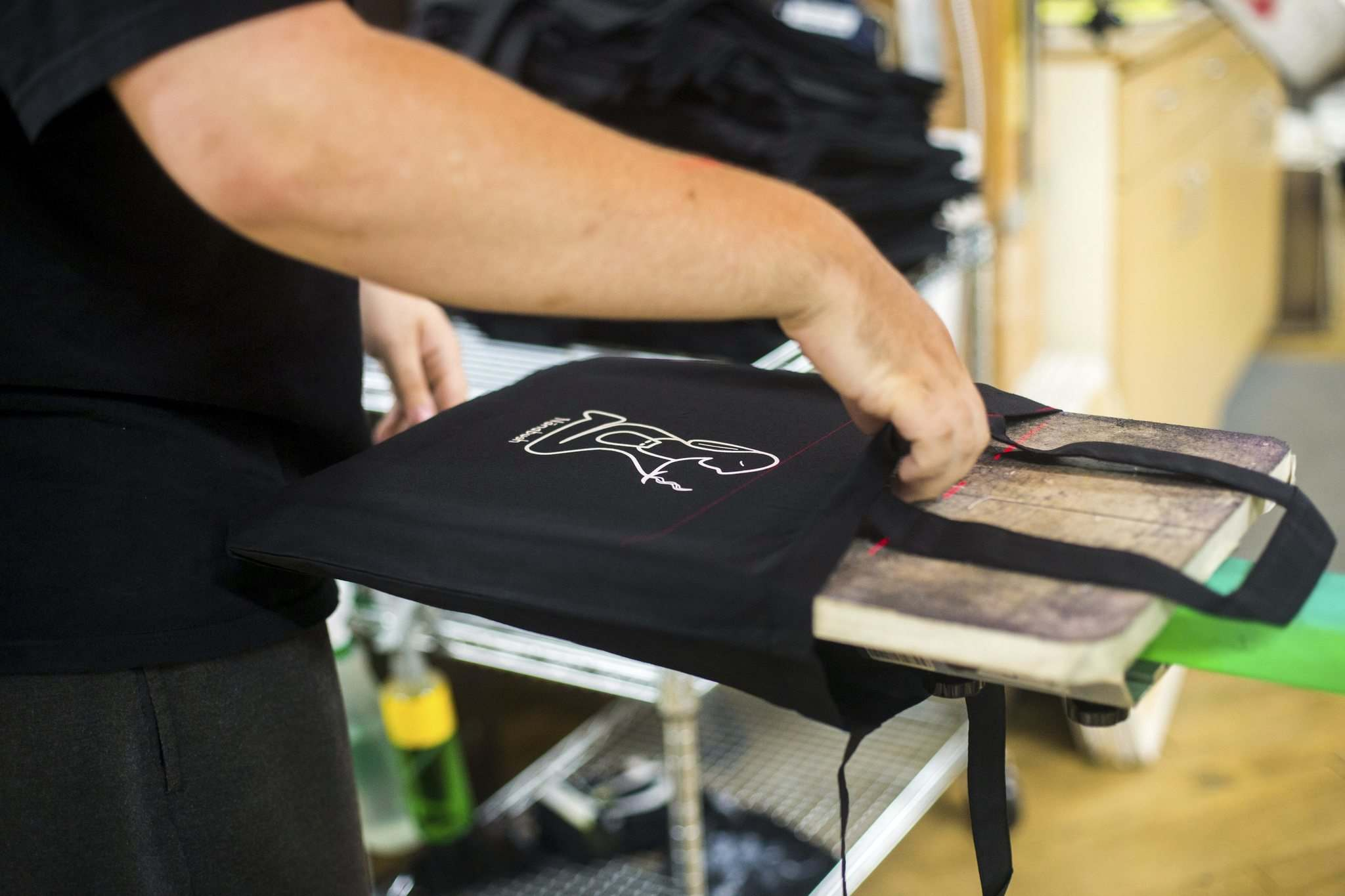 MIKAELA MACKENZIE / WINNIPEG FREE PRESS</p><p>Riley Taylor works on printing tote bags at the Floodway Print Co. in their new space in the exchange district in Winnipeg on Thursday, Aug. 16, 2018.</p><p>Winnipeg Free Press 2018.</p>