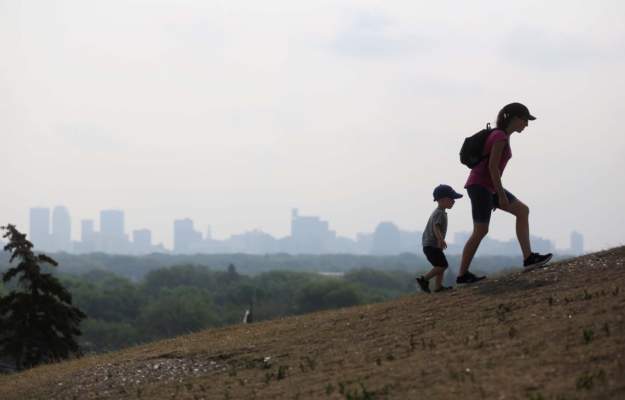 Allison Heinrichs and her son Kolton, 2, walk up Garbage Hill in front of smoke from forest fires in B.C. in August. (Trevor Hagan / Free Press files) </p>