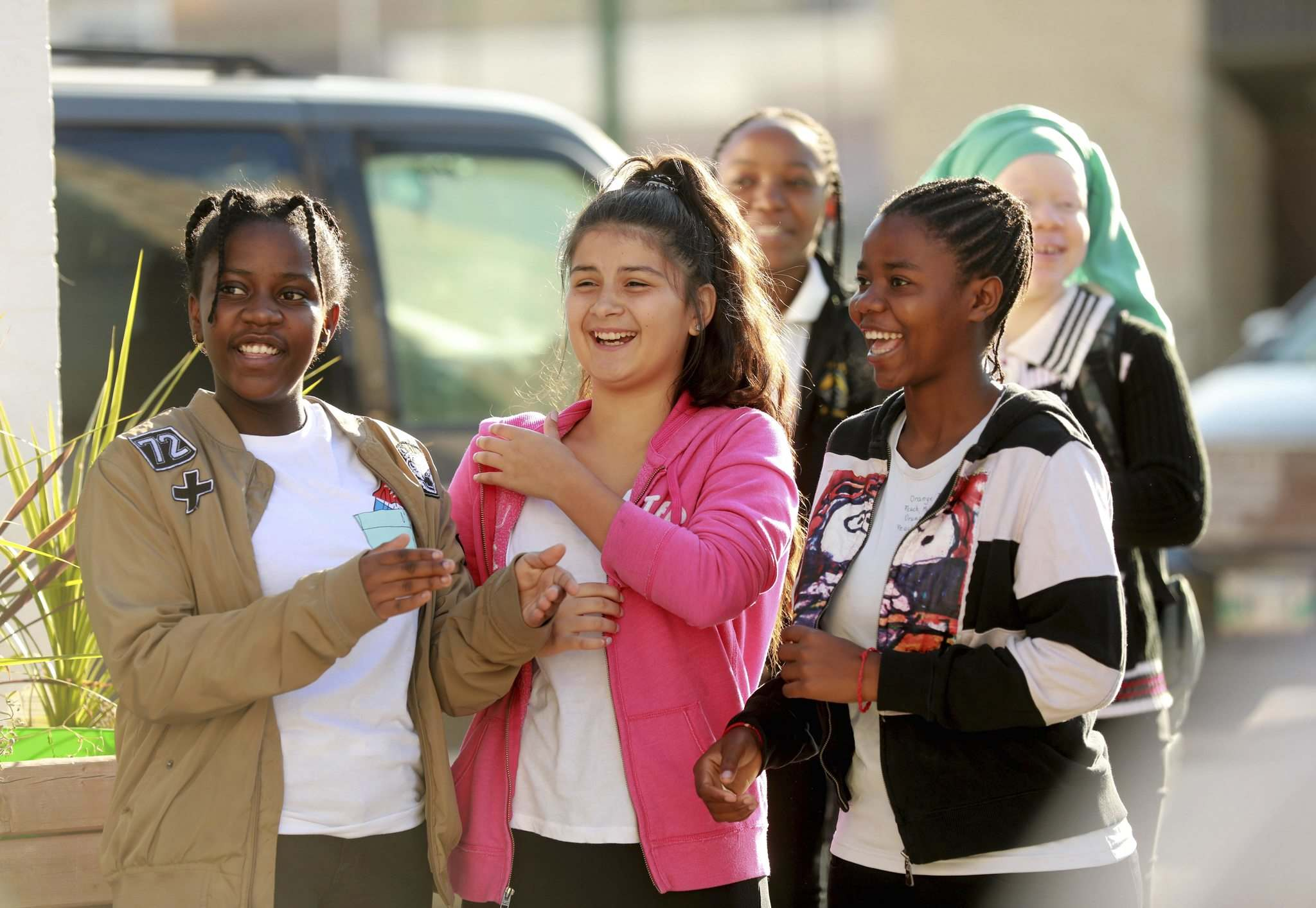 Plamedie Gatoro, left, Gabrielle Gonzalez and Christina Dusabimana celebrate the first day of their new school along with other students and teachers during ribbon cutting ceremony Wednesday.
