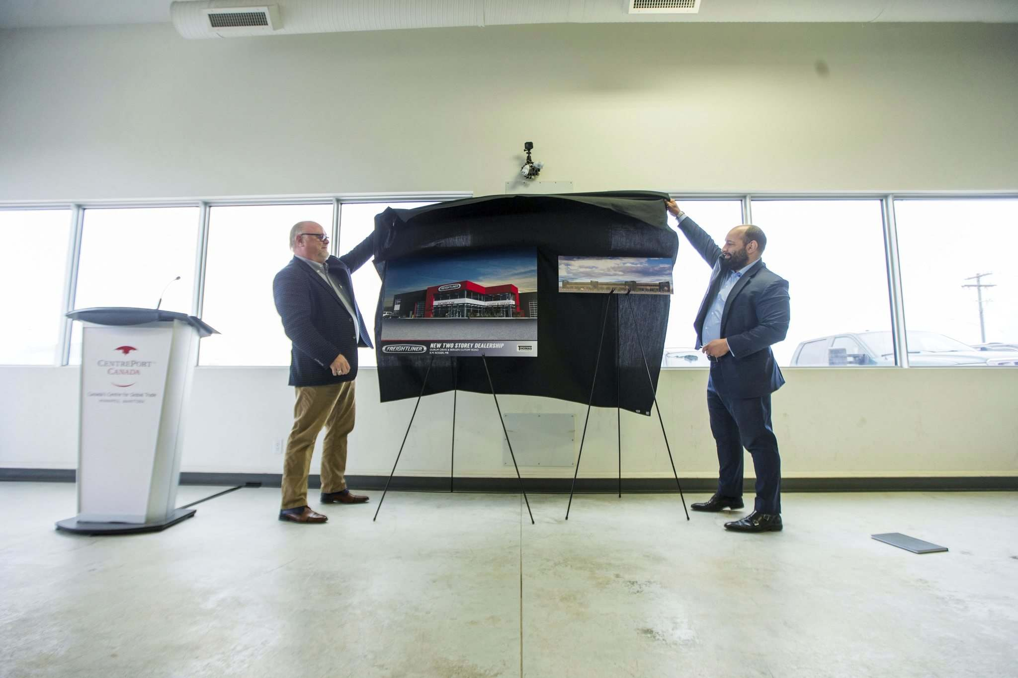 MIKAELA MACKENZIE / WINNIPEG FREE PRESS</p><p>Ken Talbot (left), president of Freightliner Manitoba, and Chris Macsymic unveil renderings of their new planned facilities at Brookside Industrial Park Phase III on Thursday.</p></p>
