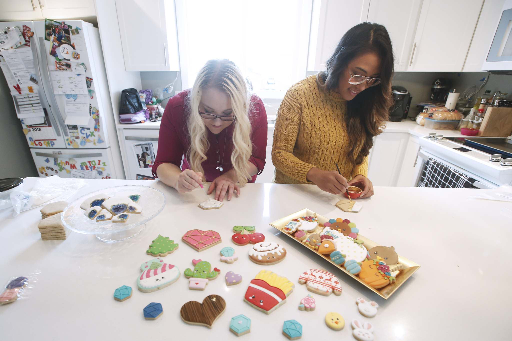 Strauman (left) and Vendivil at work. 'You do not want to watch TV with either of us,' Vendivil says. 'We're forever hitting pause and taking pictures of things, figuring this or that would be fun to make into a cookie one day down the road.'</p>