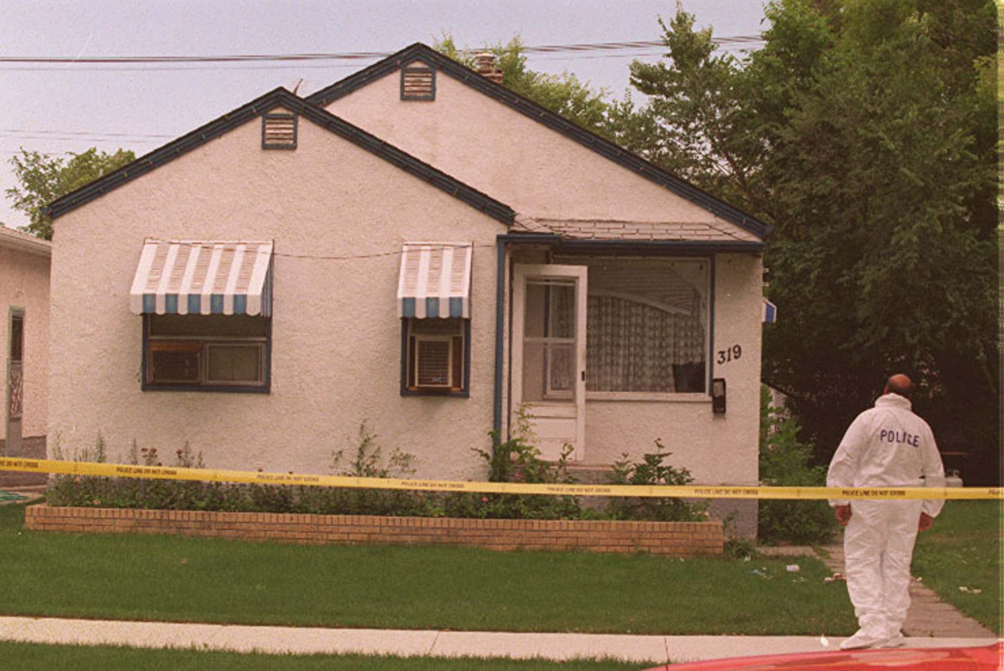 Police investigate the slayings of Russell Krowetz, Stefan Zurstegge and James Gross at 319 Semple Ave. in 1996. (Winnipeg Free Press files)</p>
