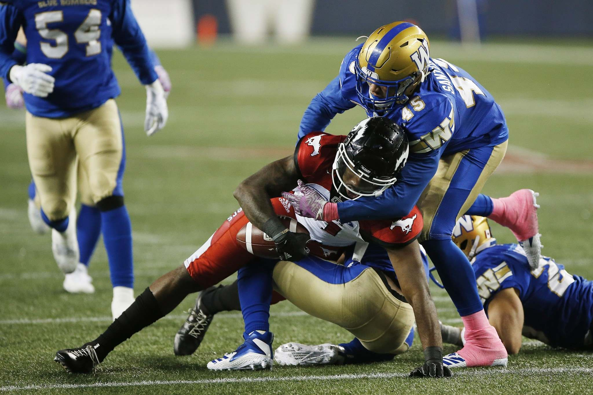Winnipeg Blue Bombers&#39; Jovan Santos-Knox (45) forces Calgary Stampeders&#39; Chris Matthews (81) to fumble the ball during the first half of CFL action Friday. JOHN WOODS / THE CANADIAN PRESS</p>