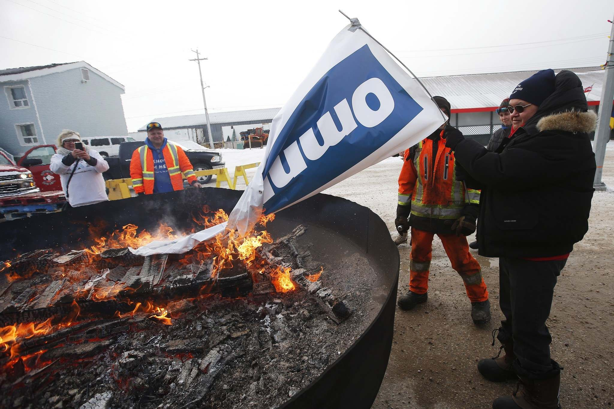 Patricia Kandiurin burns an Omnitrax banner at a party celebrating the opening of the repaired railway in Churchill. (John Woods / The Canadian Press)</p>