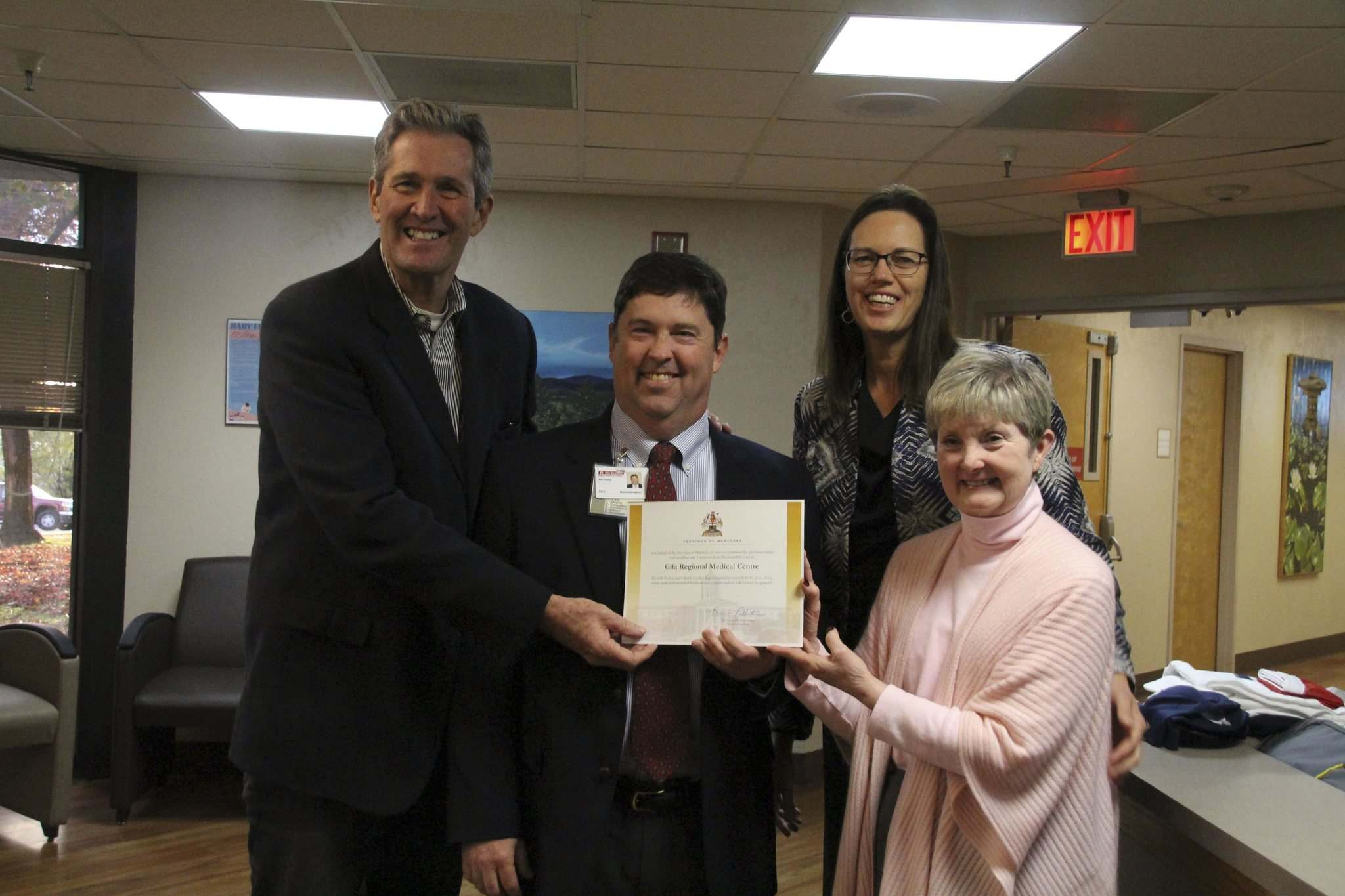 <p>Premier Brian Pallister and his wife Esther present a certificate of appreciation for the care he received at Gila Regional Medical Center in Silver City, New Mexico in 2017. GRMC Chief Financial Officer Richard Stokes and Chief Executive Officer Taffy Arias accept the certificate.</p>