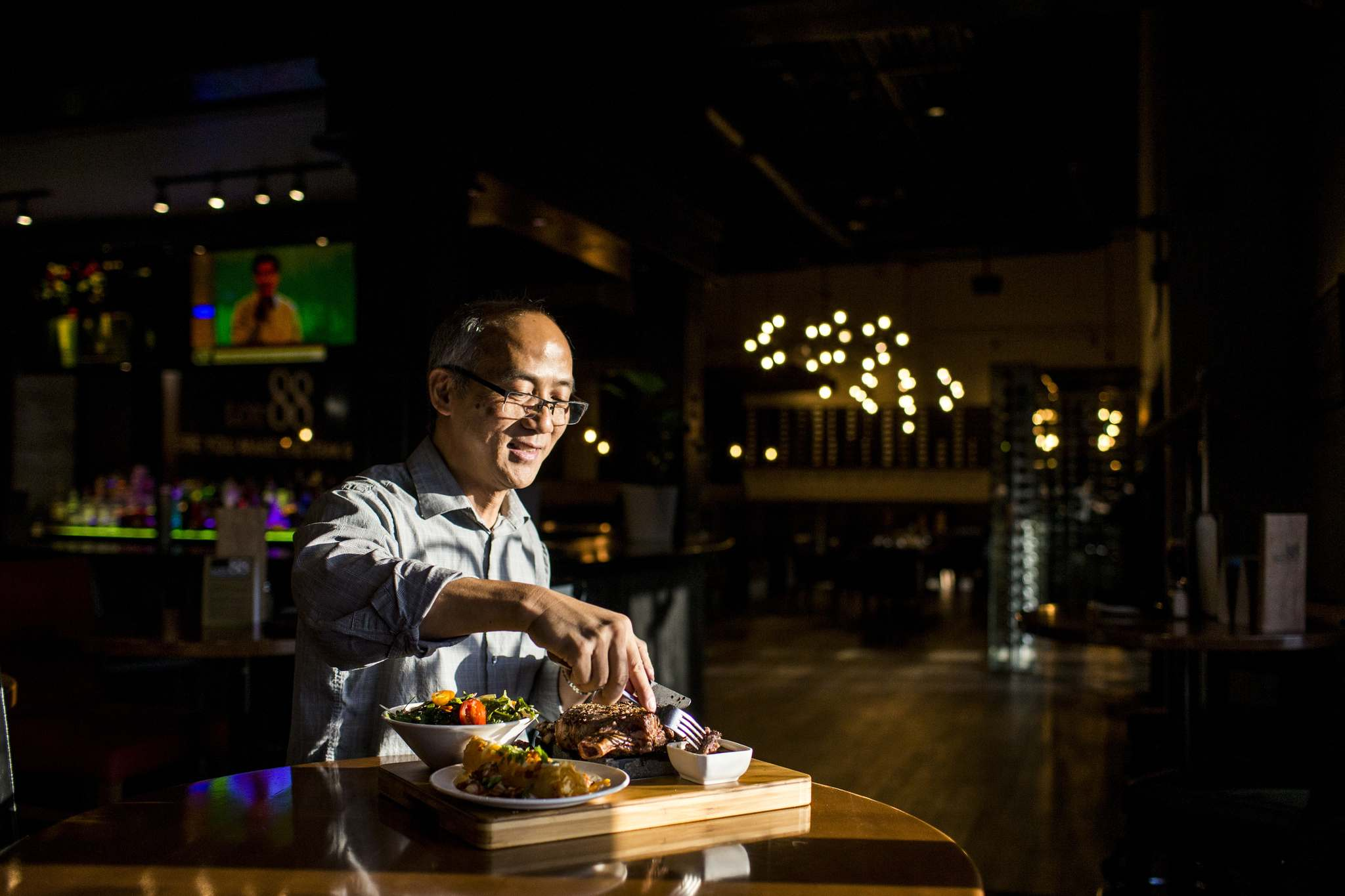 Owner Wayne Dang demonstrates the special steak-cooking technique on a lava rock.</p>