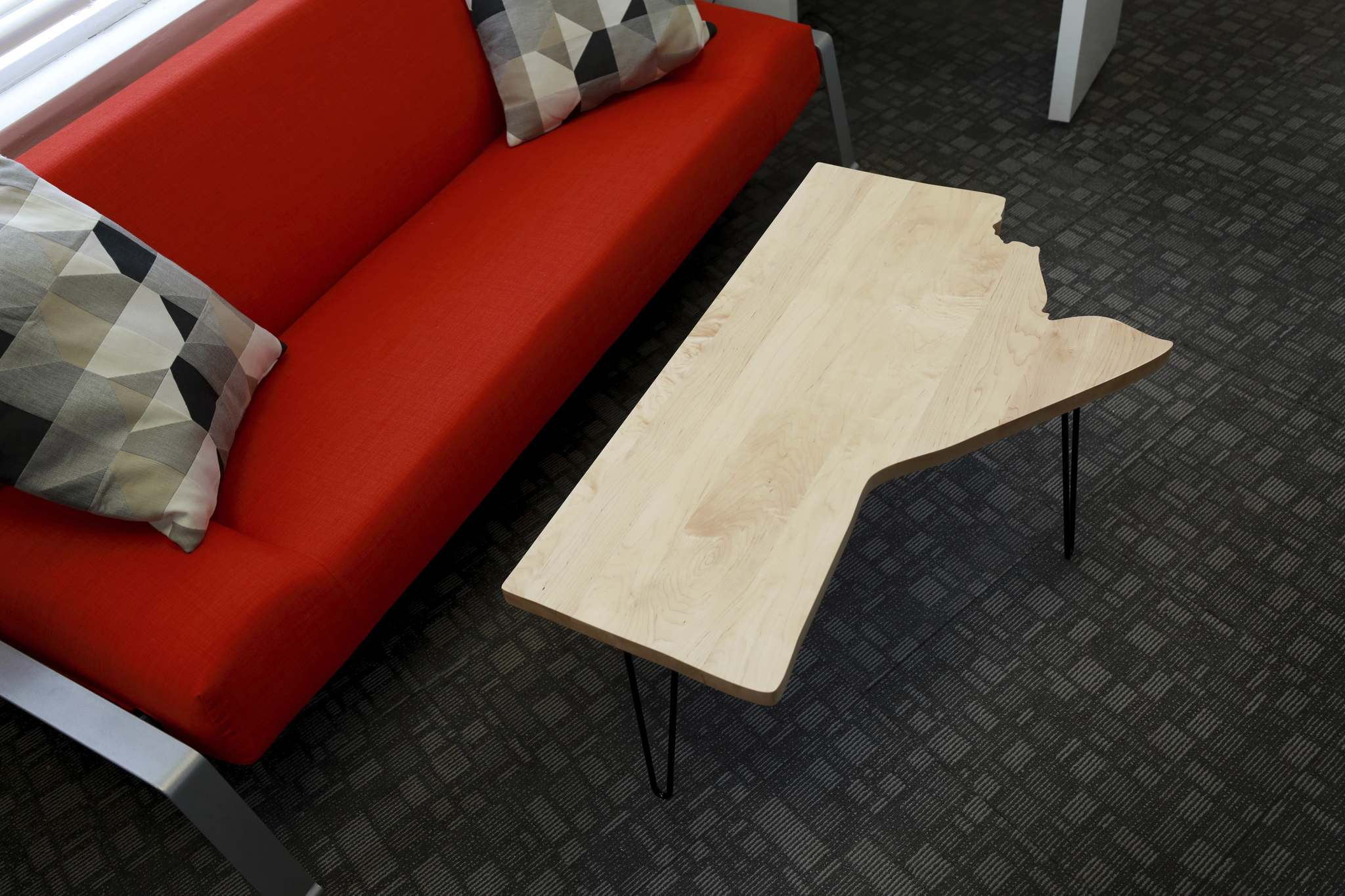 A birch wood table in the shape of Manitoba.