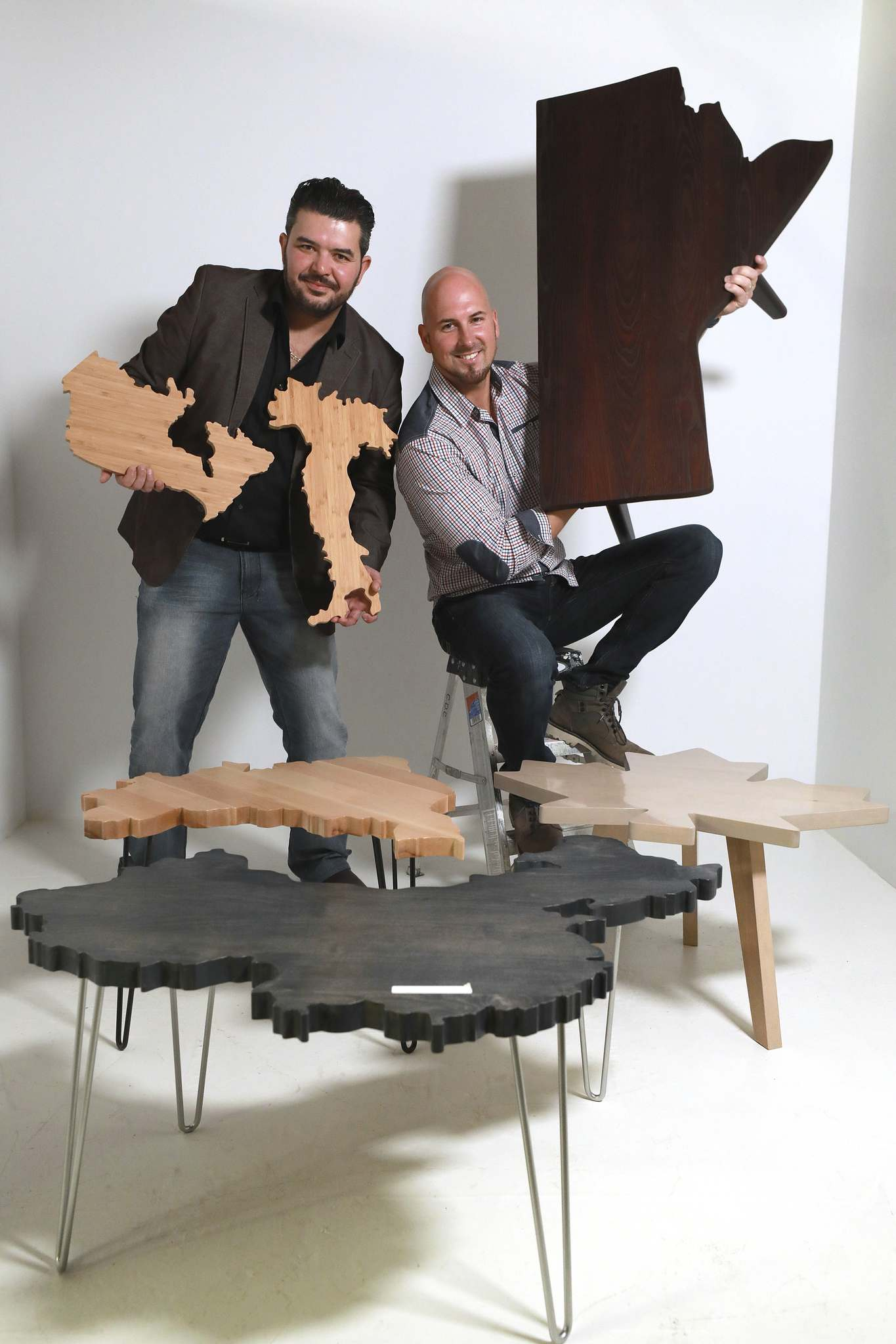 World Table Co. business partners Jason Haddad (right) and Luis Barros with a selection of their tables and boards that are cut out into shapes of countries. (Ruth Bonneville photos / Winnipeg Free Press)