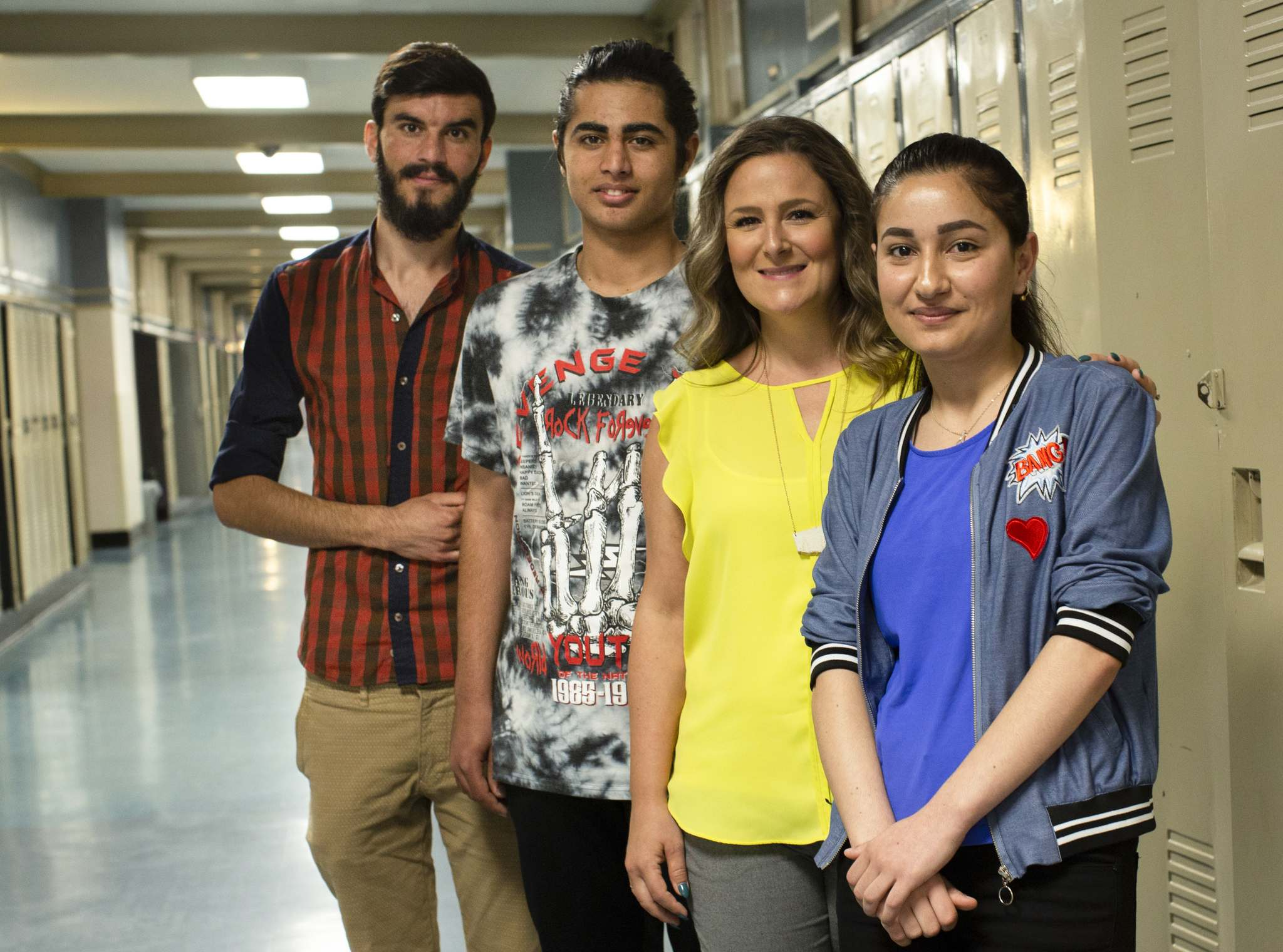 Megan Sodomsky (third from left) is a volunteer English as an Additional Language (EAL) instructor who has helped Yazidi refugees adapt to Canadian life. Students Diyar Salih (from left), Amin Murad and Aida Naso at Grant Park High School. (Andrew Ryan / Winnipeg Free Press)