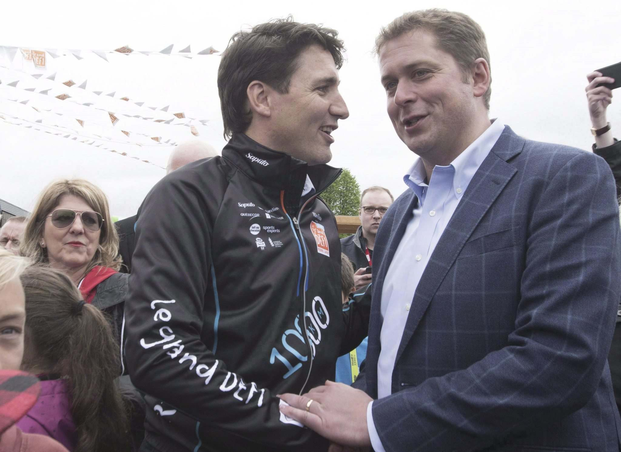 Prime Minister Justin Trudeau, left, shakes hands with Conservative Leader Andrew Scheer at the start of the Defi Pierre Lavoie, a 1000km bicycle trek in 2018 in Saguenay Que.</p>