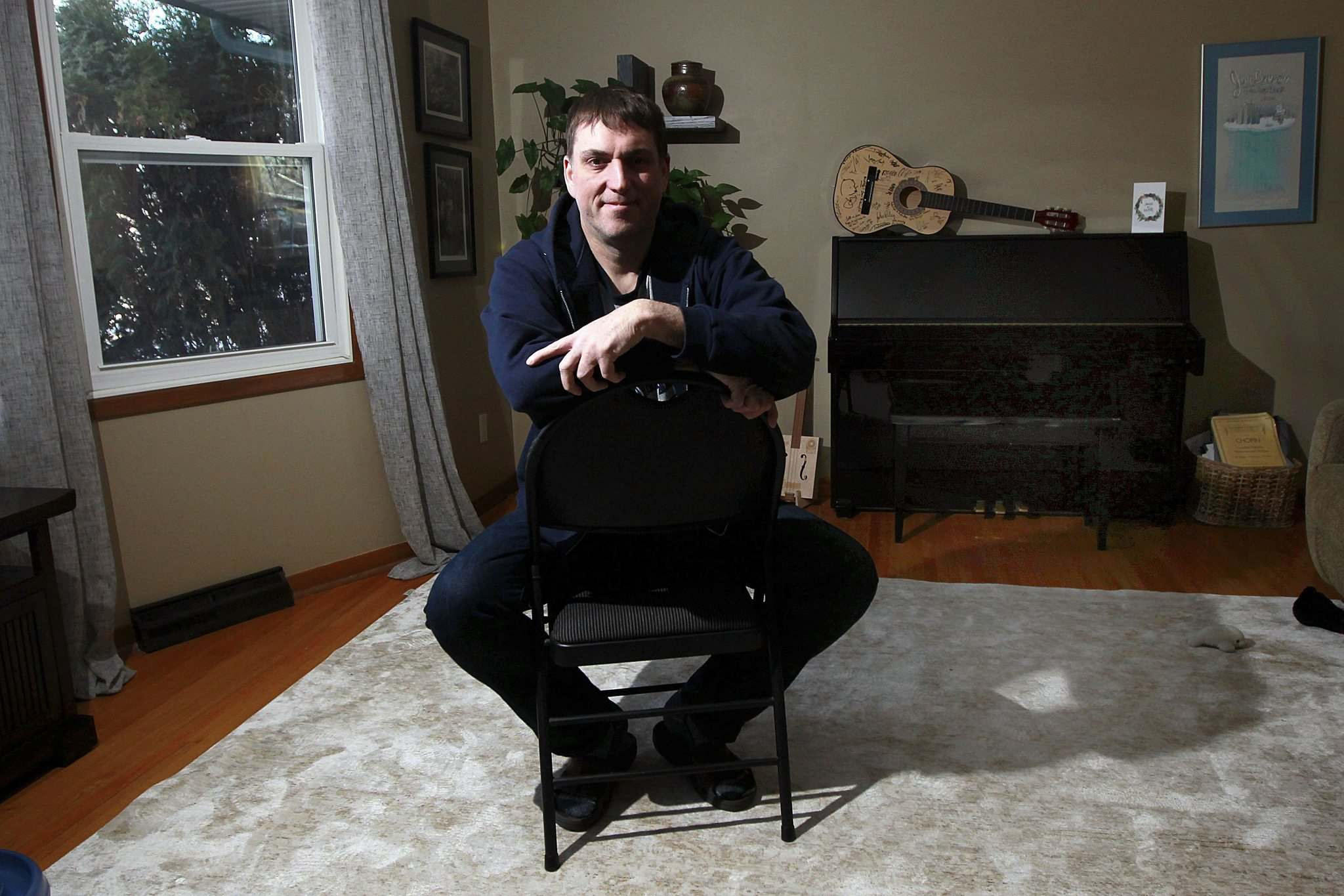 Jeff Robson relaxes in Sunset Saloon, the house concert venue created out of the living room of his Westwood home. (Phil Hossack / Winnipeg Free Press)