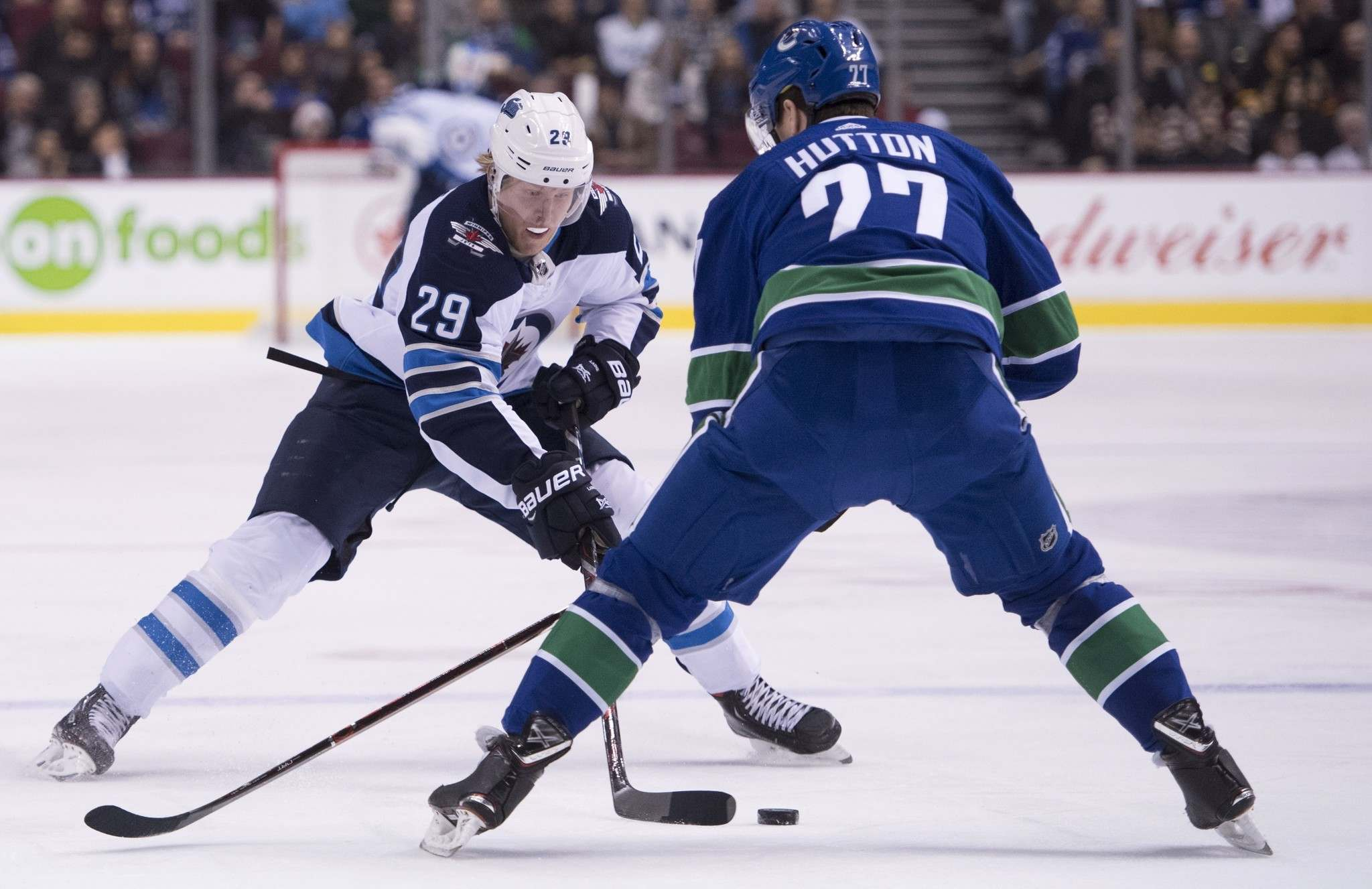 Winnipeg Jets right wing Patrik Laine (29) tries to get the puck past Vancouver Canucks defenceman Ben Hutton (27) during first-period NHL action at Rogers Arena in Vancouver last month.