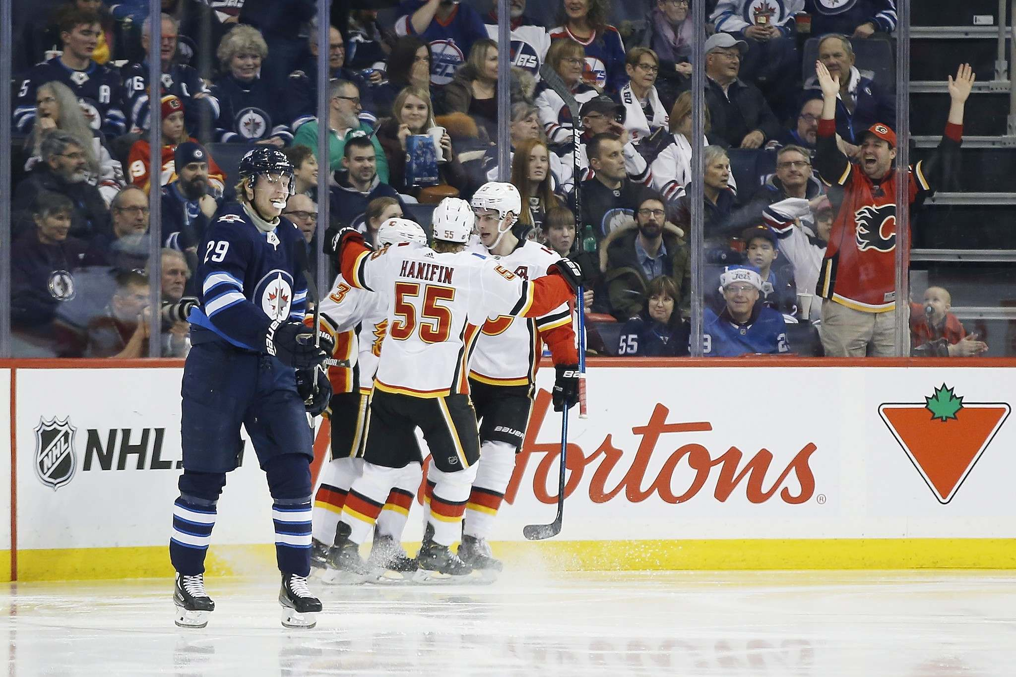 Calgary Flames' Noah Hanifin (55), Johnny Gaudreau (13) and Sean Monahan (23) celebrate Gaudreau's goal that went off the stick of Winnipeg Jets right wing Patrik Laine (29) during second period NHL action in Winnipeg last month.</p>