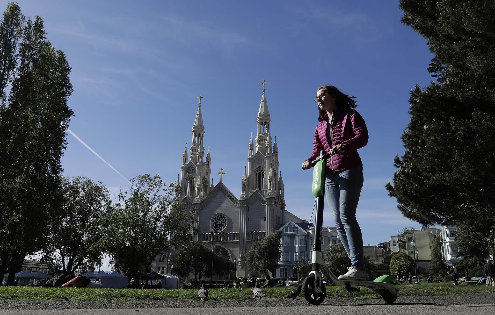 Electric scooters are designed for short trips as an alternative to a private car or taxi, and are locked and unlocked using an app. (Jeff Chiu / The Associated Press files)</p>