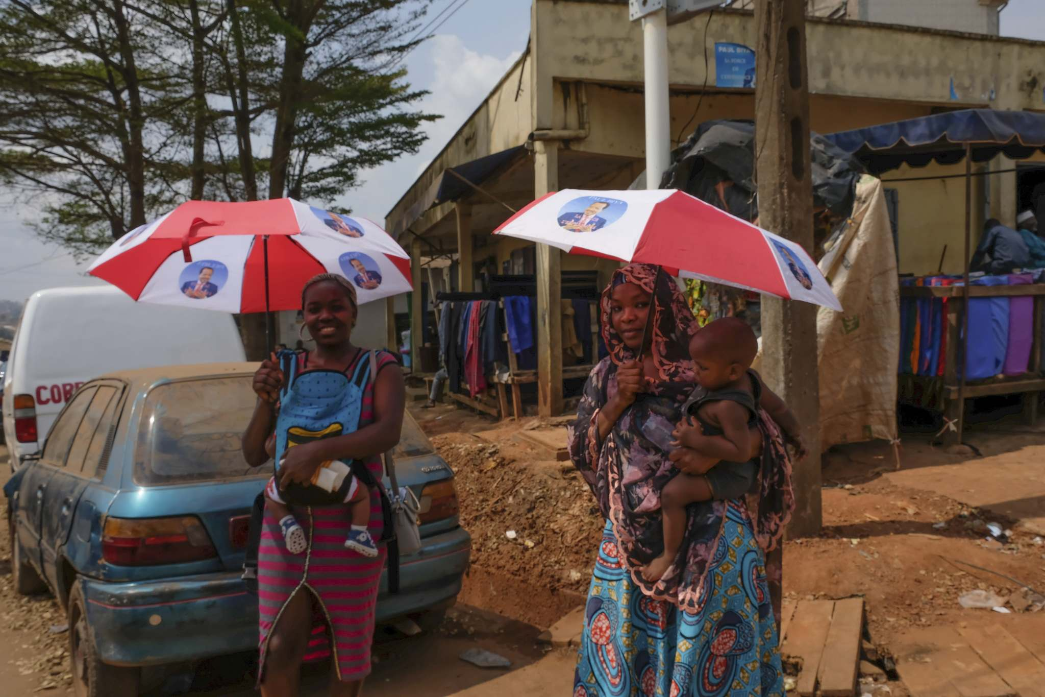 Siobhan O'Grady / washington post</p><p>Women in Yaoundé, Cameroon, carry umbrellas they received as campaign handouts featuring President Paul Biya, whose government forces have been criticized for reportedly attacking unarmed citizens in the country's anglophone villages.</p>