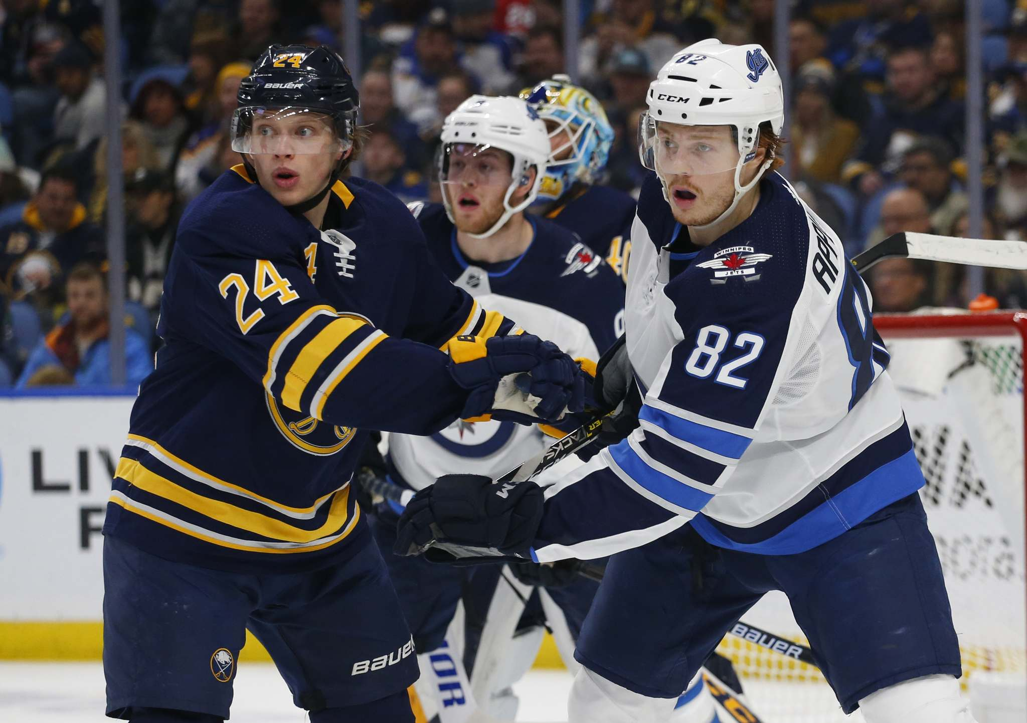 Buffalo Sabres defenseman Lawrence Pilut (24) and Winnipeg Jets forward Mason Appleton (82) battle for position during the second period of an NHL hockey game, Sunday in Buffalo N.Y.