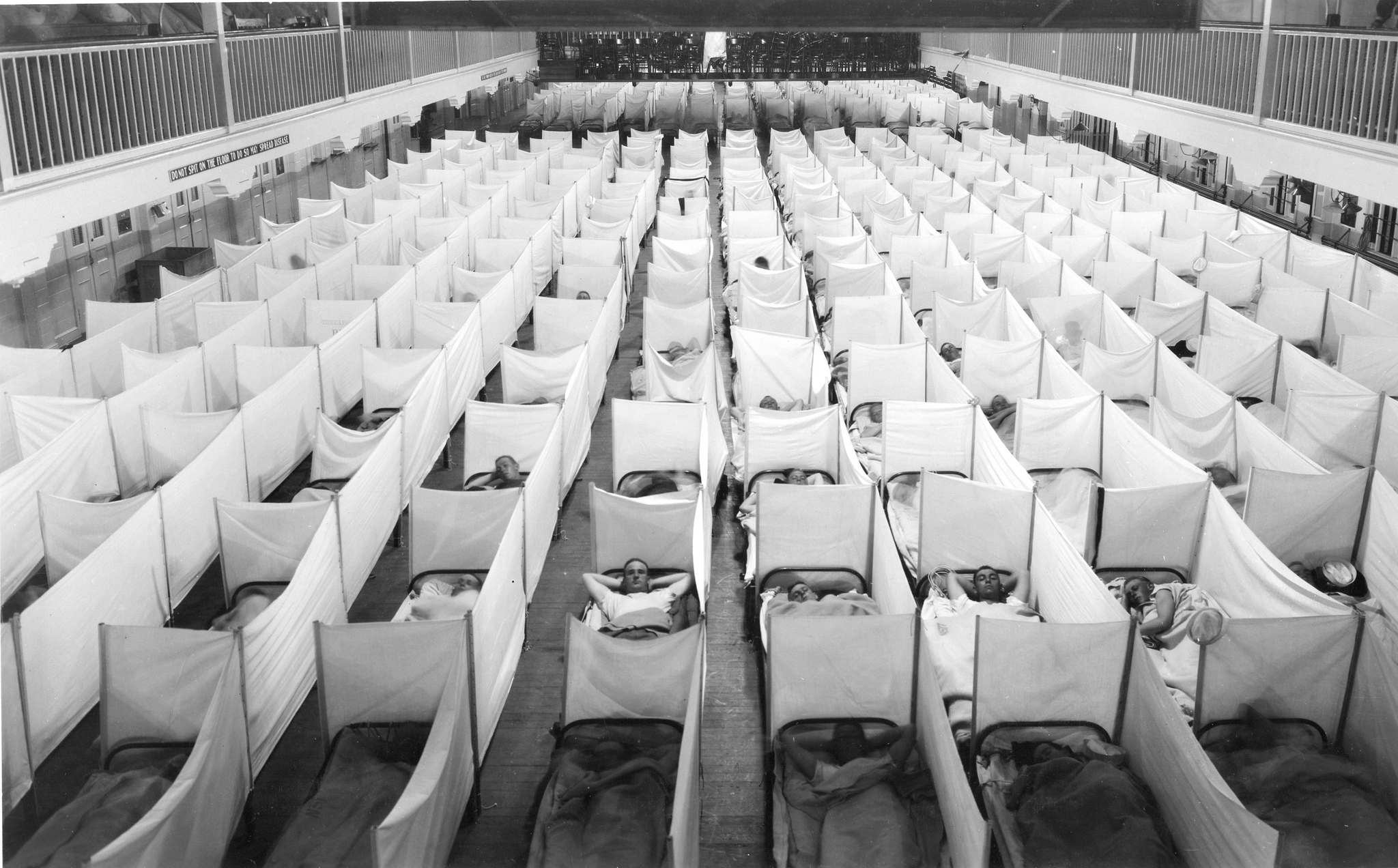 A crowded sleeping area is extemporized on the Drill Hall floor of the Main Barracks. Sneeze screens are erected as a precaution against the spread of influenza. Photographed during World War I, probably in the latter part of 1918. Signs on the wall at left forbid spitting on the floor.