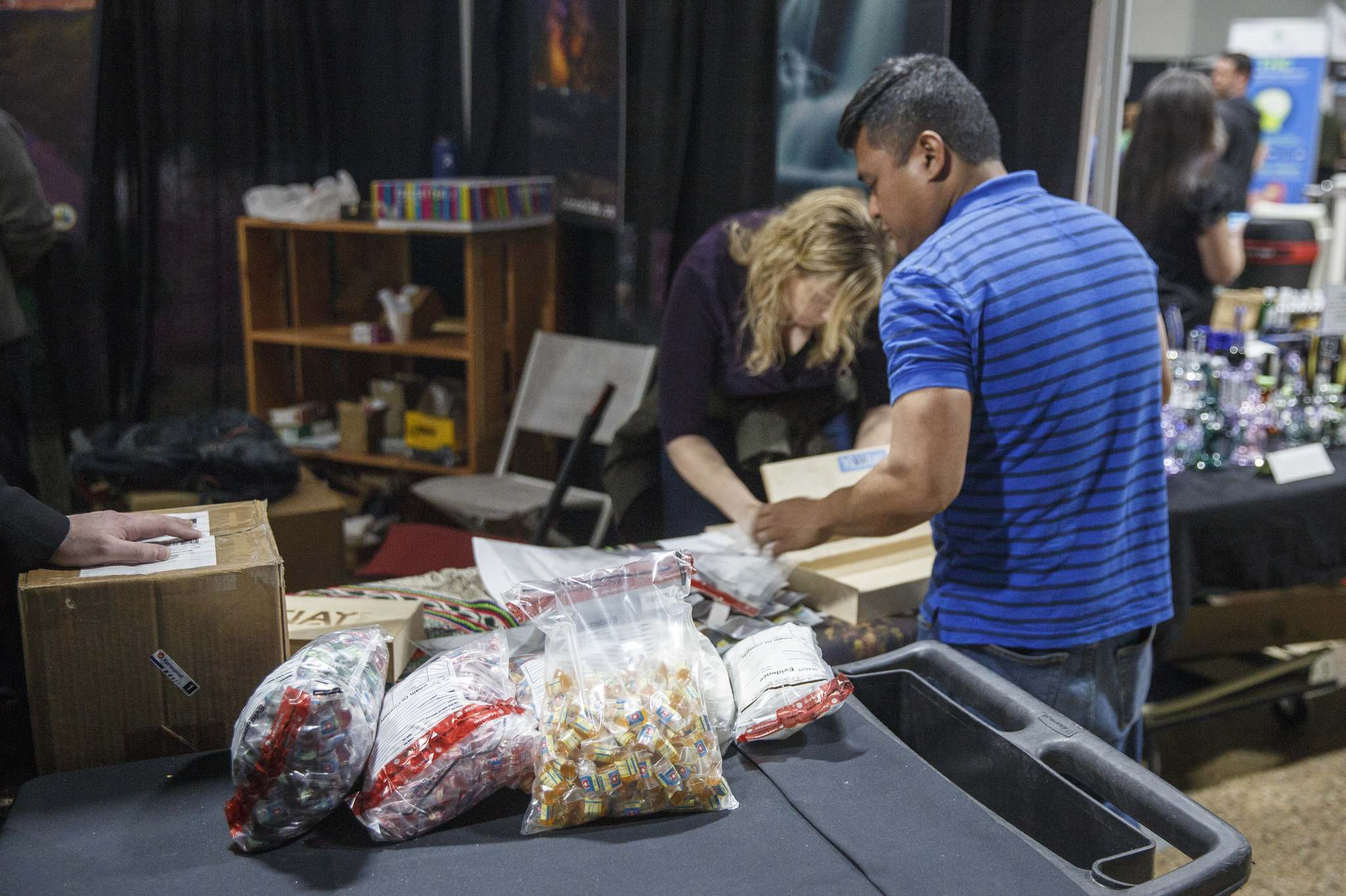 Investigators pack up illegal edible products that contain THC in the Kootenay Labs Booth at the Hempfest Canada Expo in Winnipeg in February. The sellers were ticketed and fined. (Mike Deal / Winnipeg Free Press files)