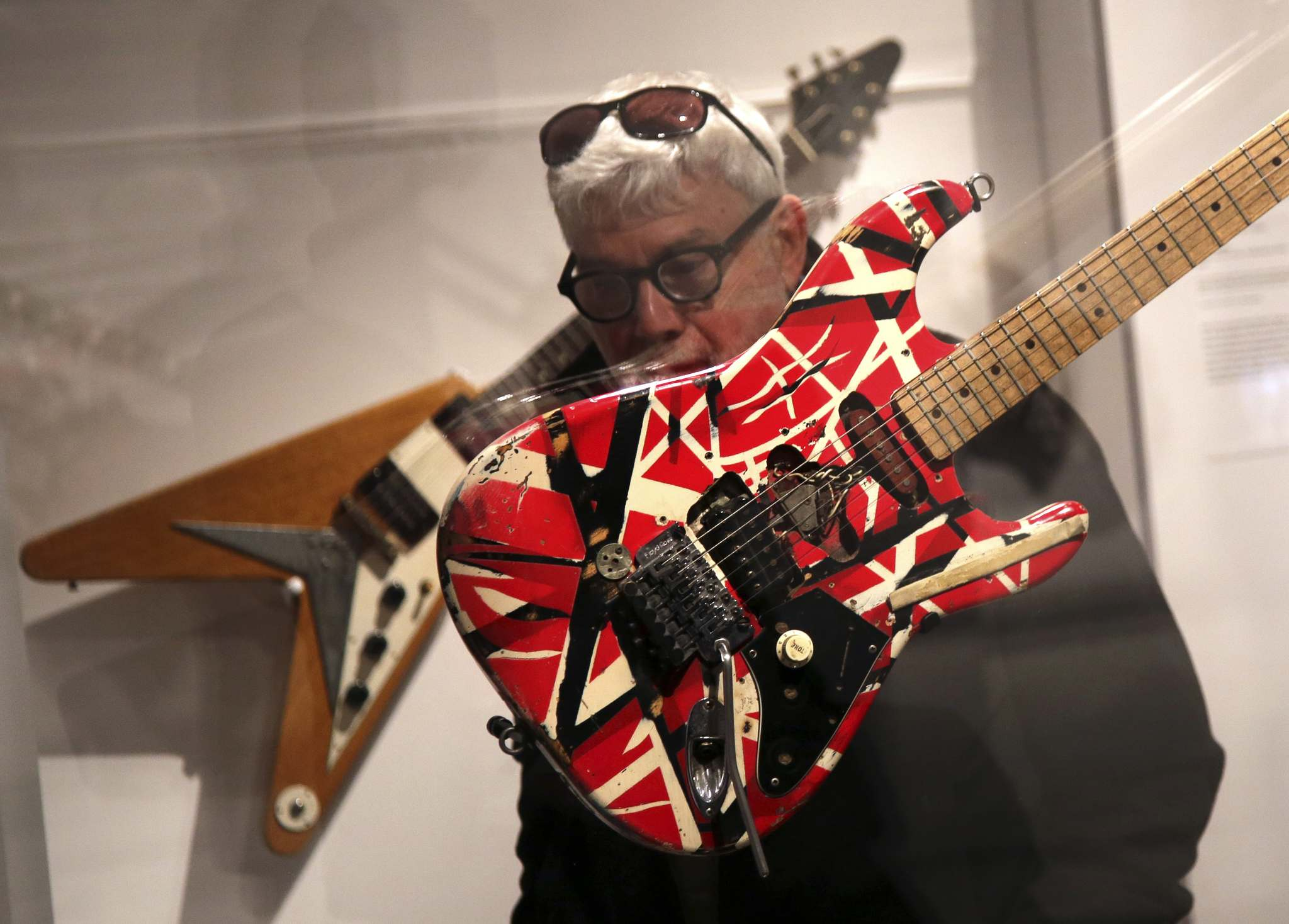 "A man inspects a guitar made and played by Eddie Van Halen during a press preview of the exhibit ""Play It Loud: Instruments of Rock & Roll,"" at the Metropolitan Museum of Art in New York, Monday, April 1, 2019. The exhibit, which showcases the instruments of rock and roll legends, opens to the public on April 8 and runs until Oct. 1, 2019. (AP Photo/Seth Wenig)</p>"