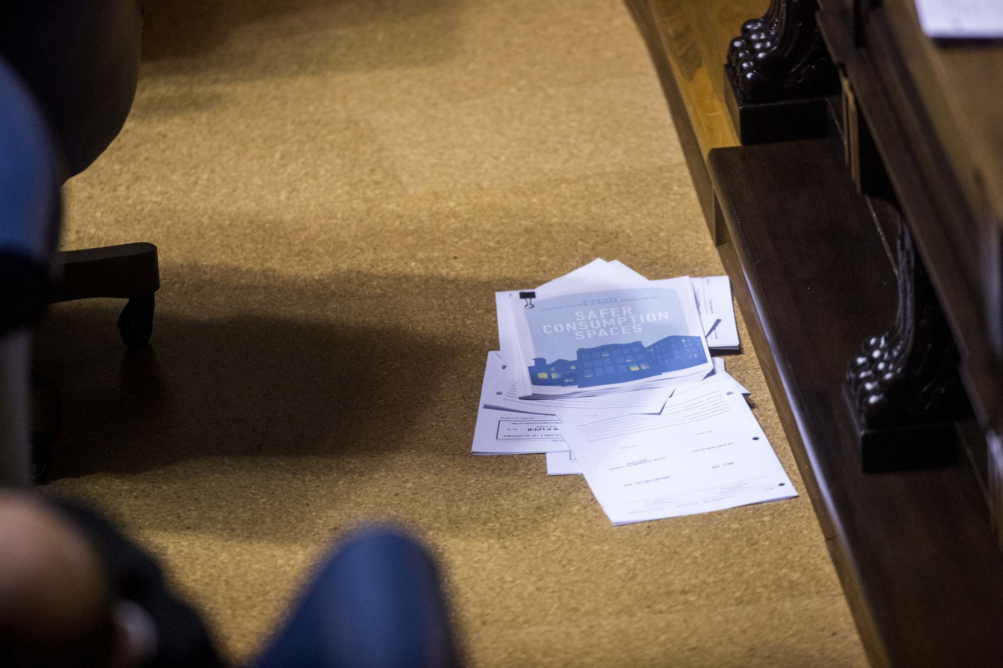 <p>The pages of a report on safe consumption sites on the floor behind Pallister at the Manitoba Legislative Building on Monday.</p>